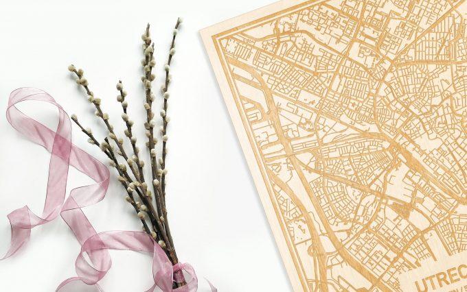 Hier ligt de houten plattegrond Utrecht naast een bloemetje als gepersonaliseerd cadeau voor haar.