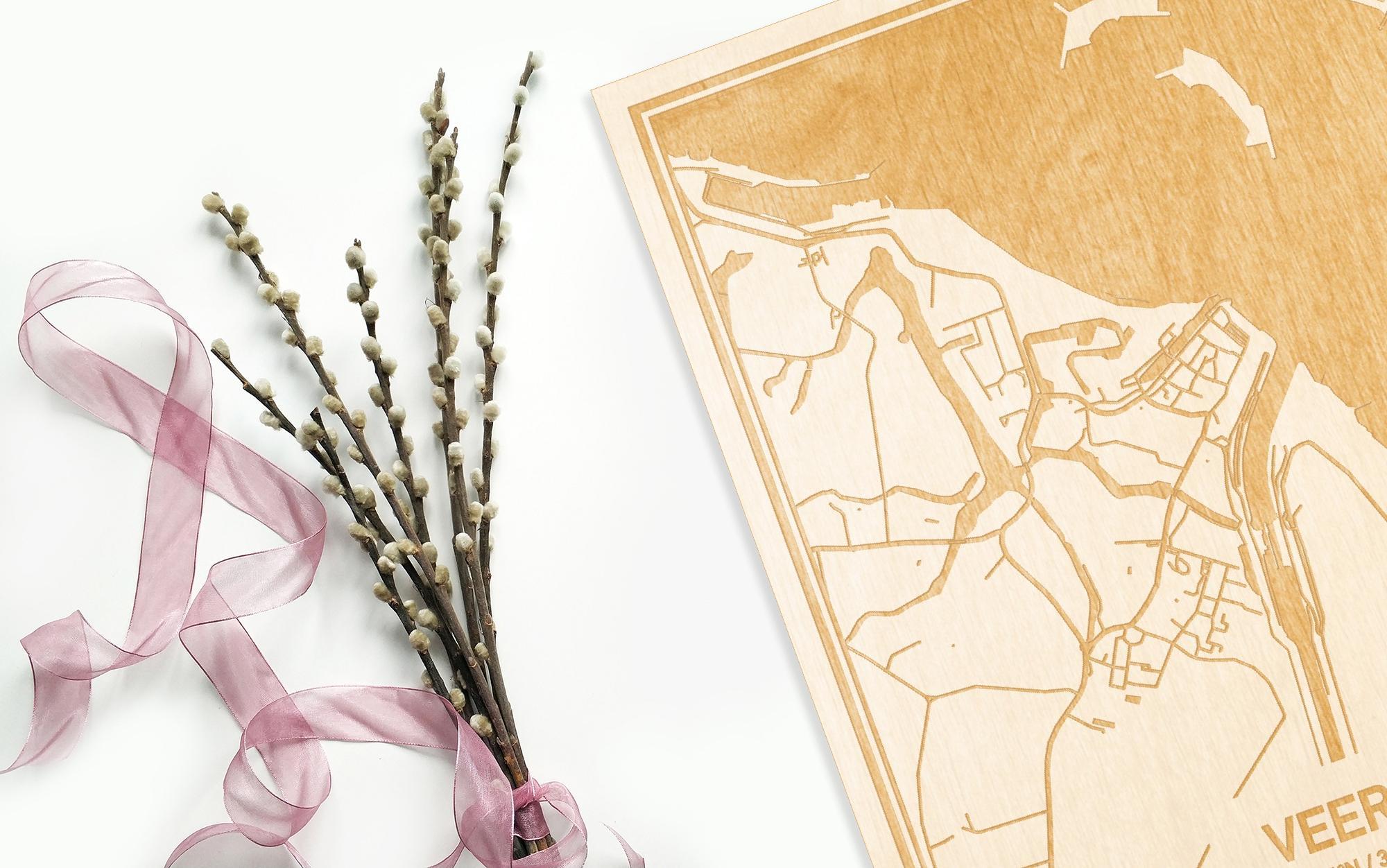 Hier ligt de houten plattegrond Veere naast een bloemetje als gepersonaliseerd cadeau voor haar.