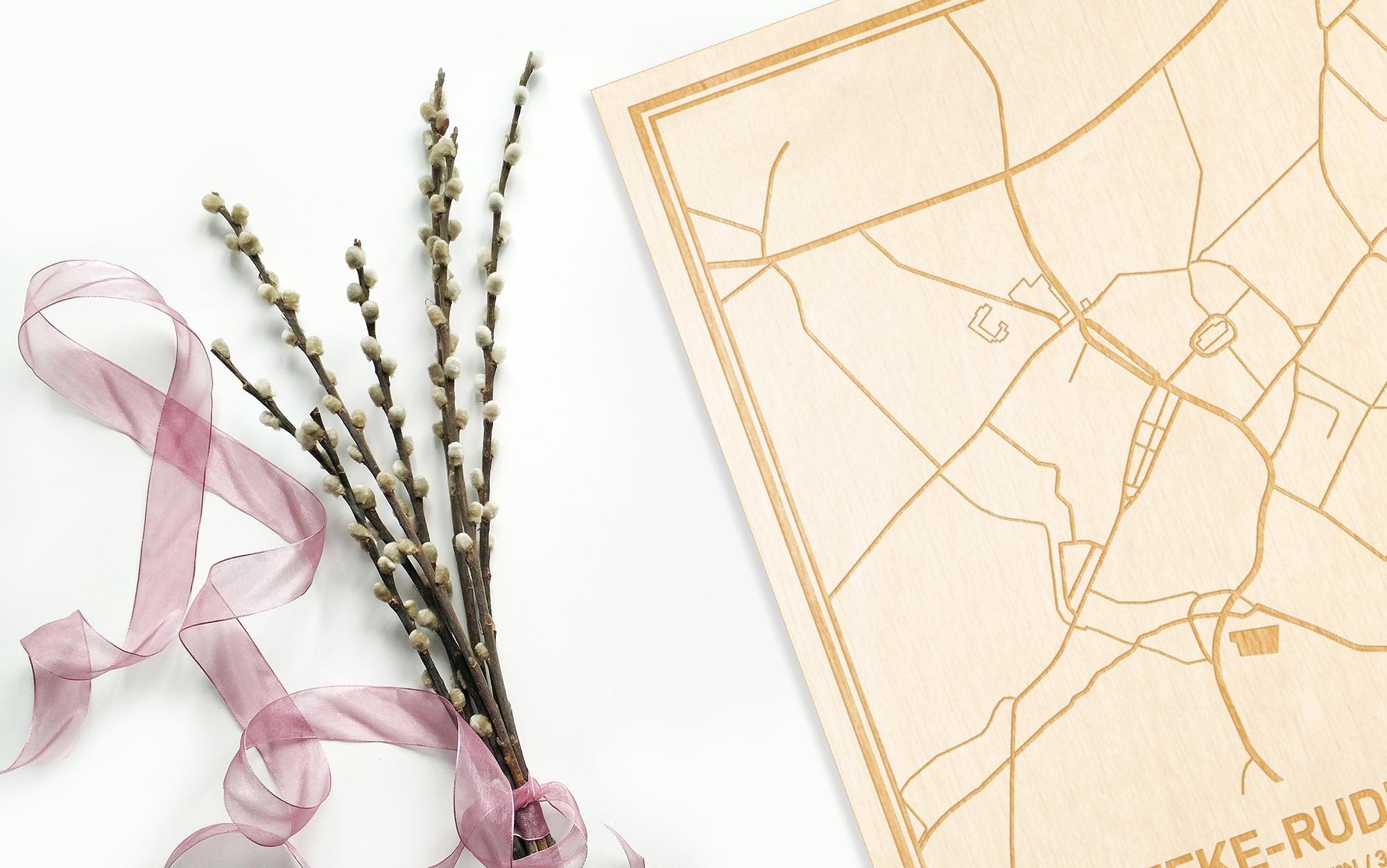 Hier ligt de houten plattegrond Velzeke-Ruddershove naast een bloemetje als gepersonaliseerd cadeau voor haar.