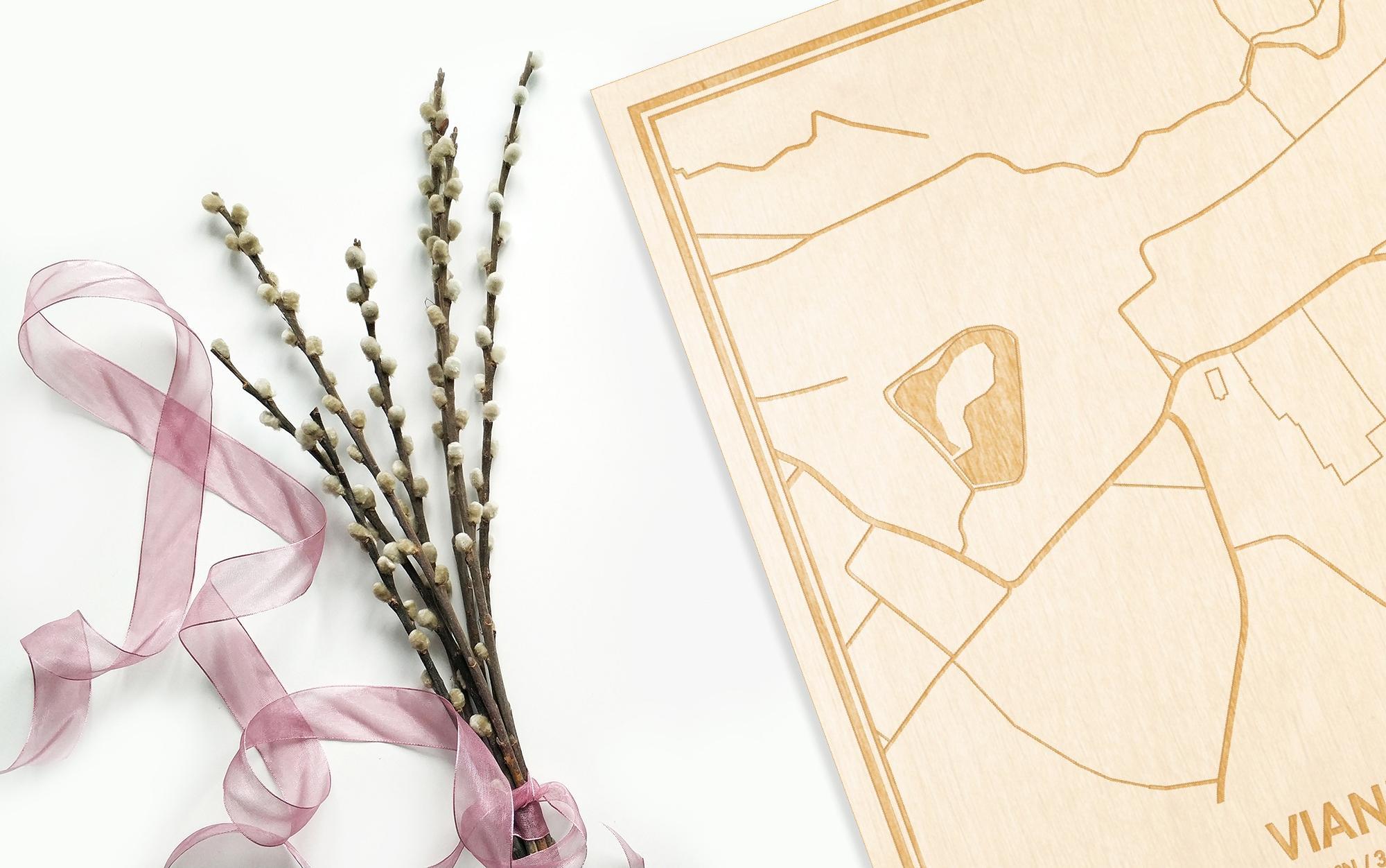 Hier ligt de houten plattegrond Viane naast een bloemetje als gepersonaliseerd cadeau voor haar.