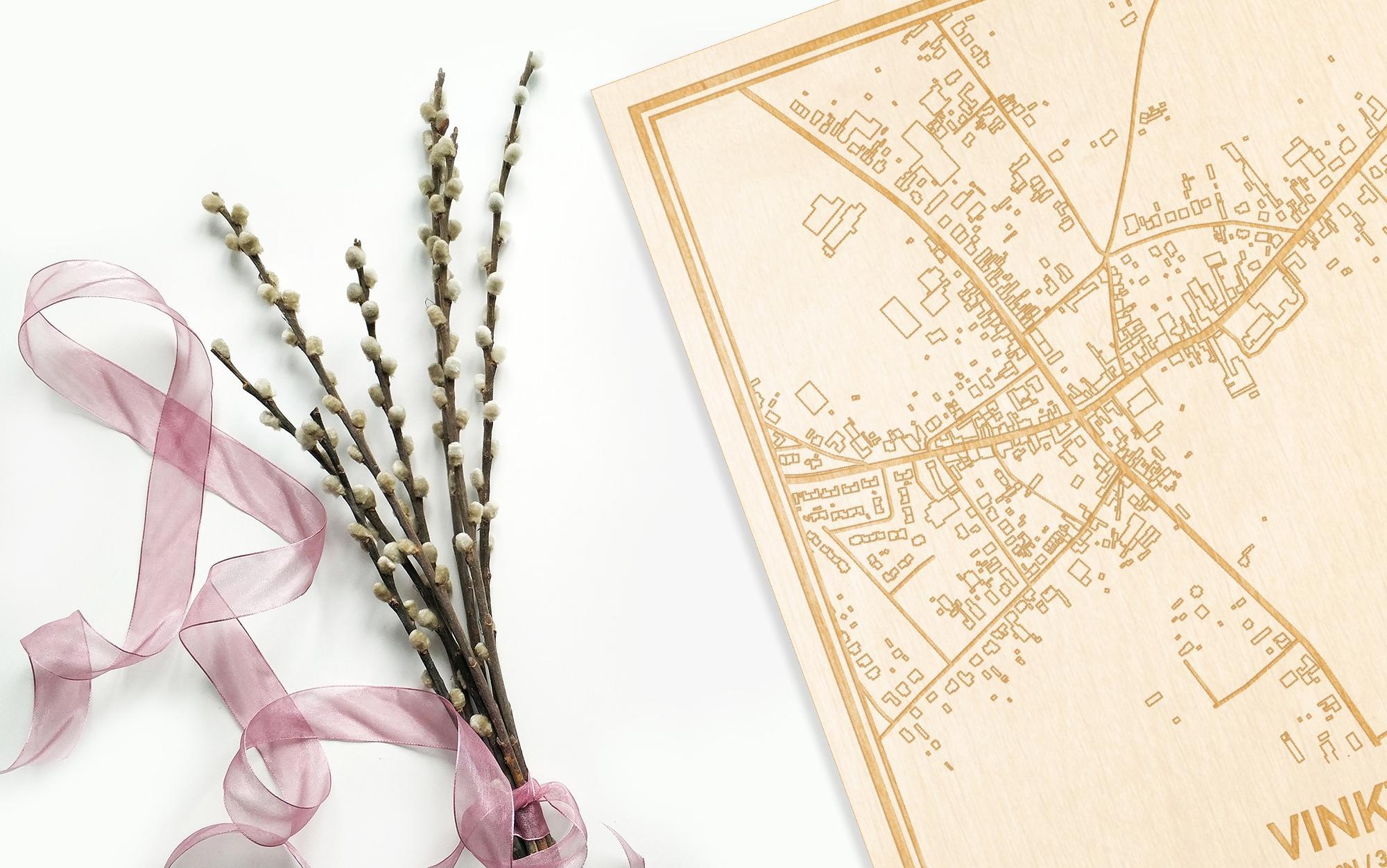Hier ligt de houten plattegrond Vinkt naast een bloemetje als gepersonaliseerd cadeau voor haar.
