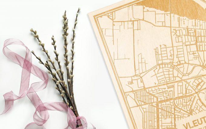Hier ligt de houten plattegrond Vleuten naast een bloemetje als gepersonaliseerd cadeau voor haar.