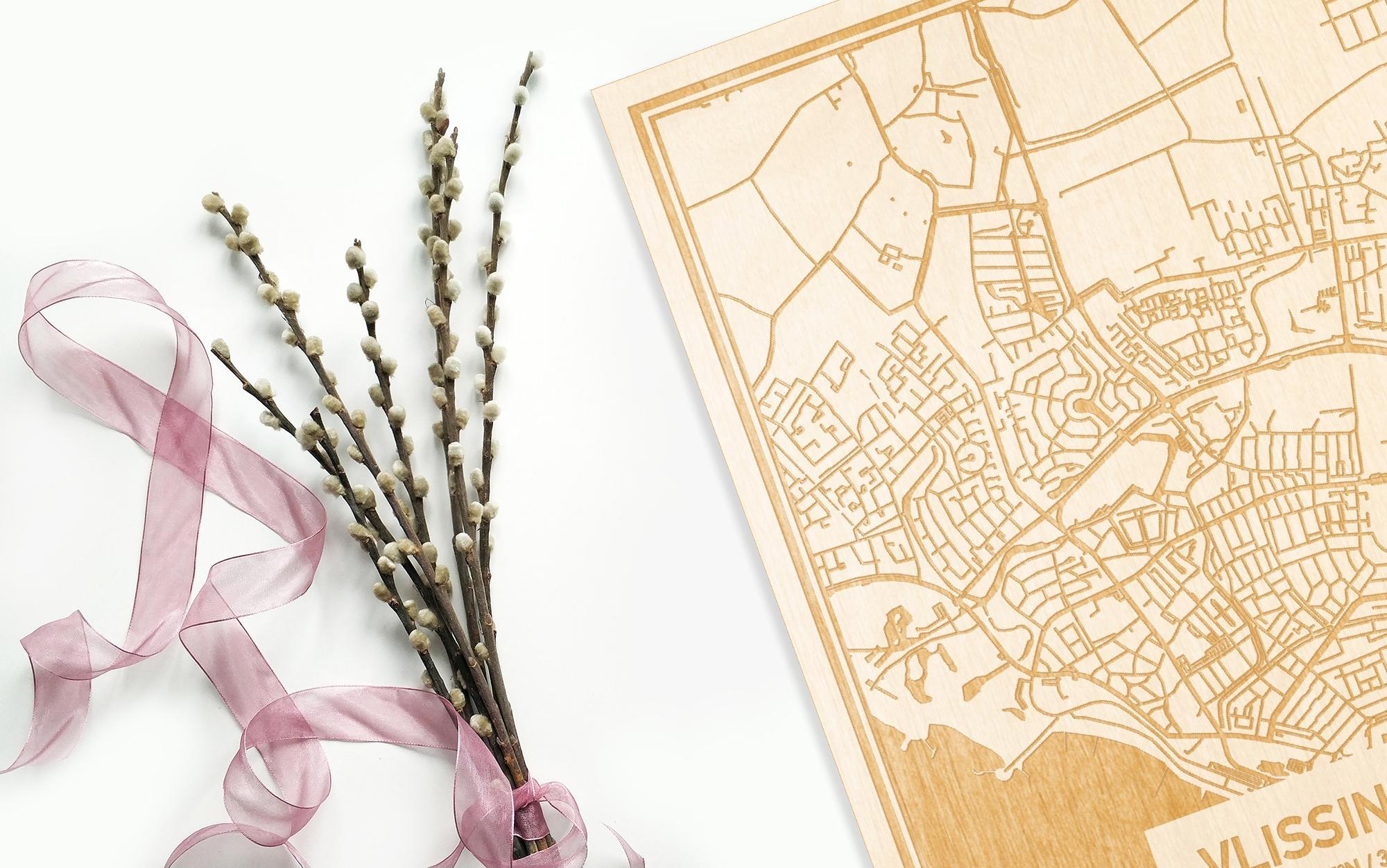Hier ligt de houten plattegrond Vlissingen naast een bloemetje als gepersonaliseerd cadeau voor haar.