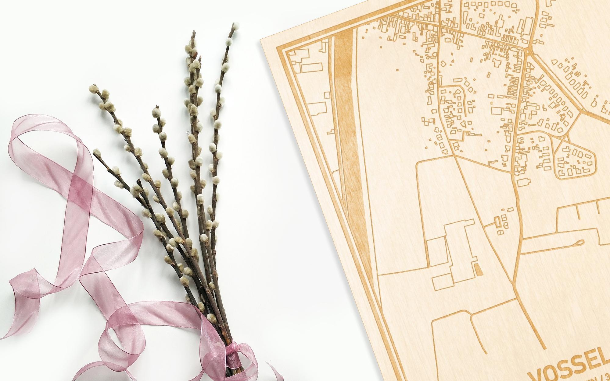 Hier ligt de houten plattegrond Vosselare naast een bloemetje als gepersonaliseerd cadeau voor haar.