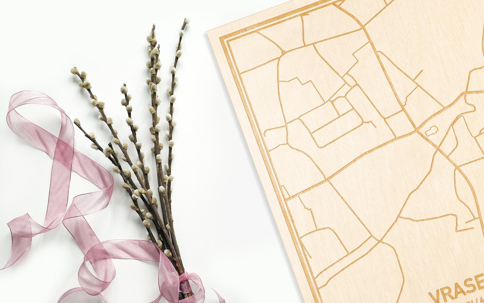 Hier ligt de houten plattegrond Vrasene naast een bloemetje als gepersonaliseerd cadeau voor haar.