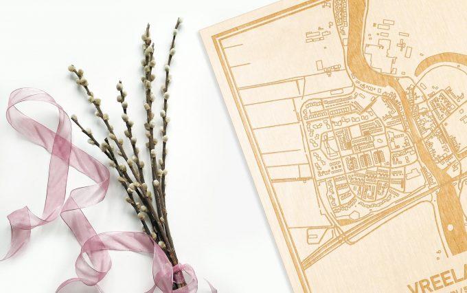 Hier ligt de houten plattegrond Vreeland naast een bloemetje als gepersonaliseerd cadeau voor haar.