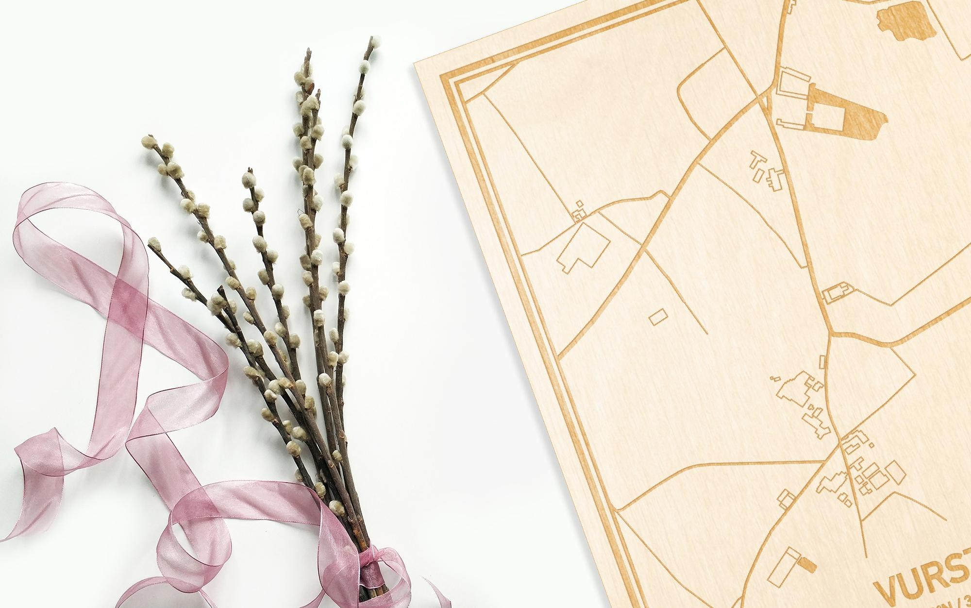 Hier ligt de houten plattegrond Vurste naast een bloemetje als gepersonaliseerd cadeau voor haar.