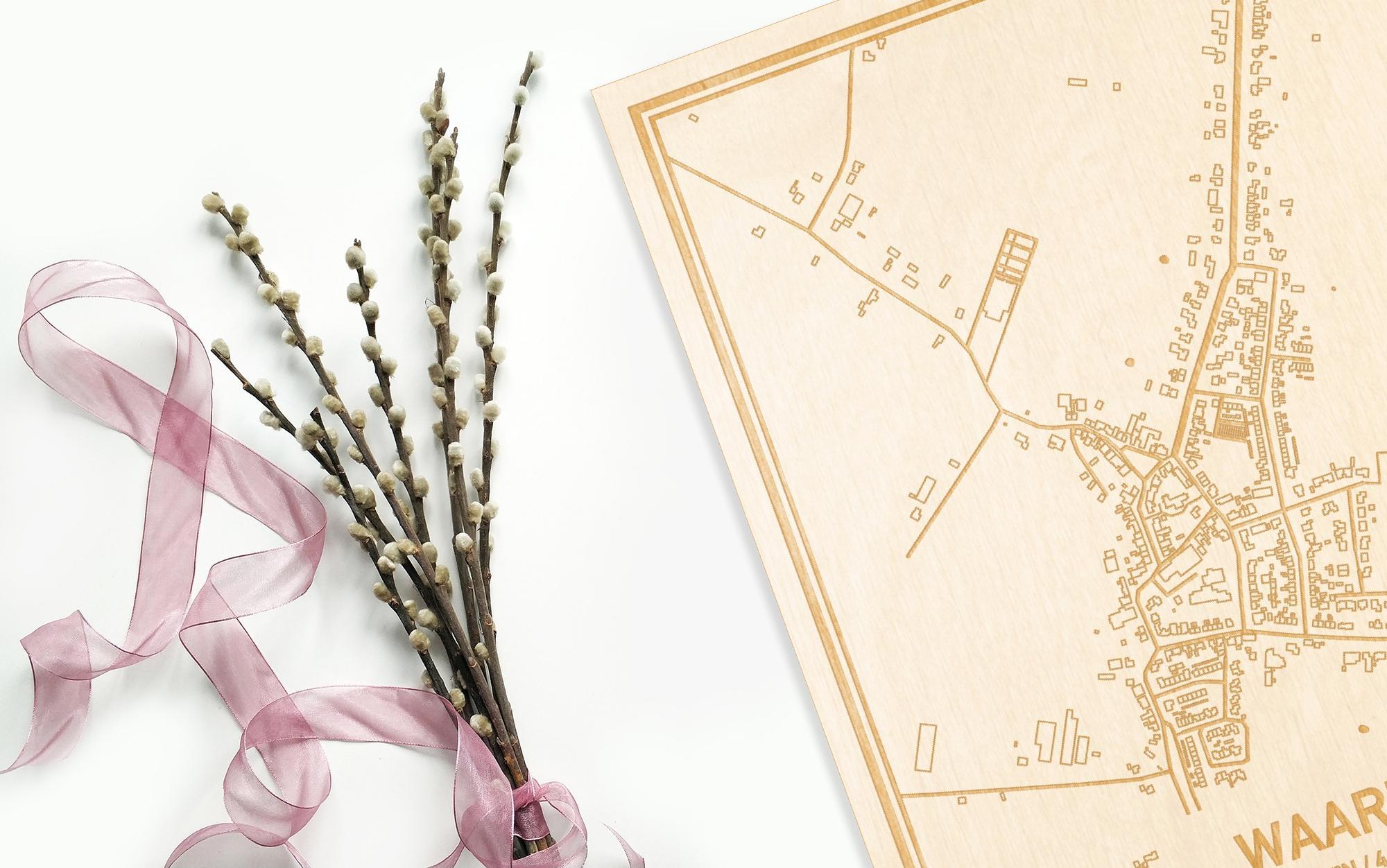 Hier ligt de houten plattegrond Waarde naast een bloemetje als gepersonaliseerd cadeau voor haar.