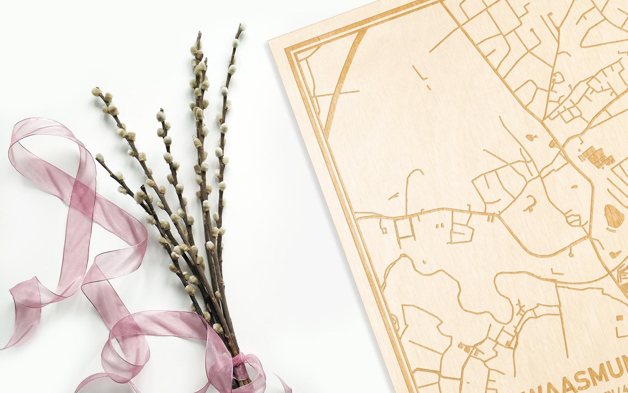 Hier ligt de houten plattegrond Waasmunster naast een bloemetje als gepersonaliseerd cadeau voor haar.