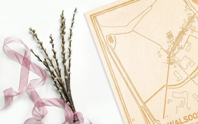 Hier ligt de houten plattegrond Walsoorden naast een bloemetje als gepersonaliseerd cadeau voor haar.