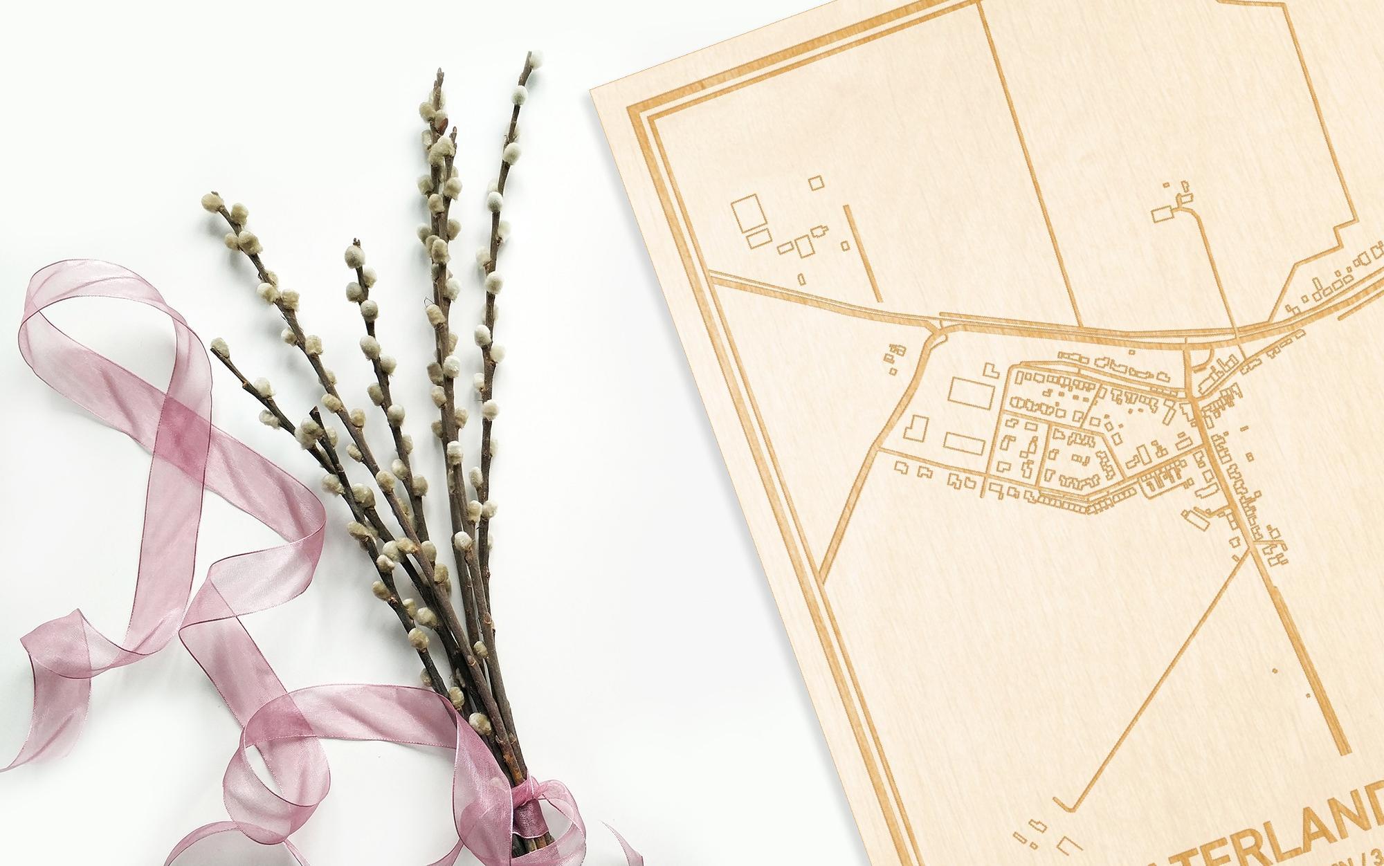 Hier ligt de houten plattegrond Waterlandkerkje naast een bloemetje als gepersonaliseerd cadeau voor haar.