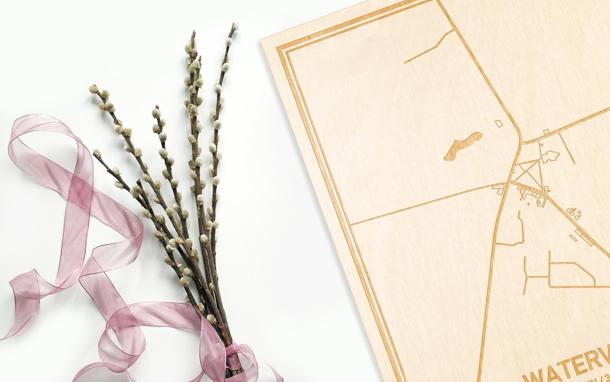Hier ligt de houten plattegrond Watervliet naast een bloemetje als gepersonaliseerd cadeau voor haar.
