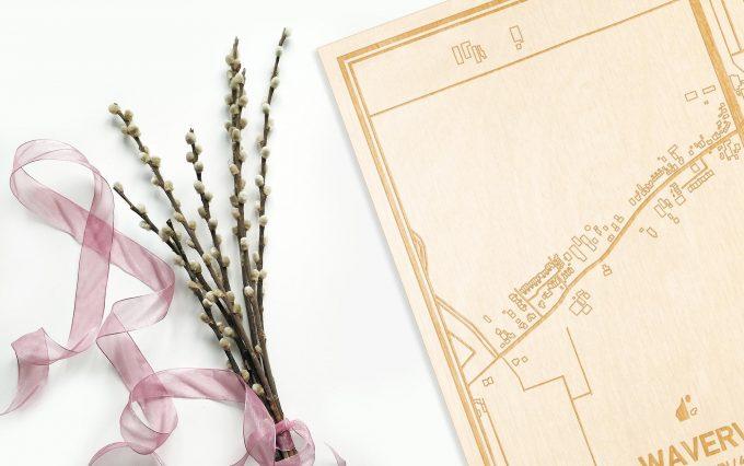 Hier ligt de houten plattegrond Waverveen naast een bloemetje als gepersonaliseerd cadeau voor haar.