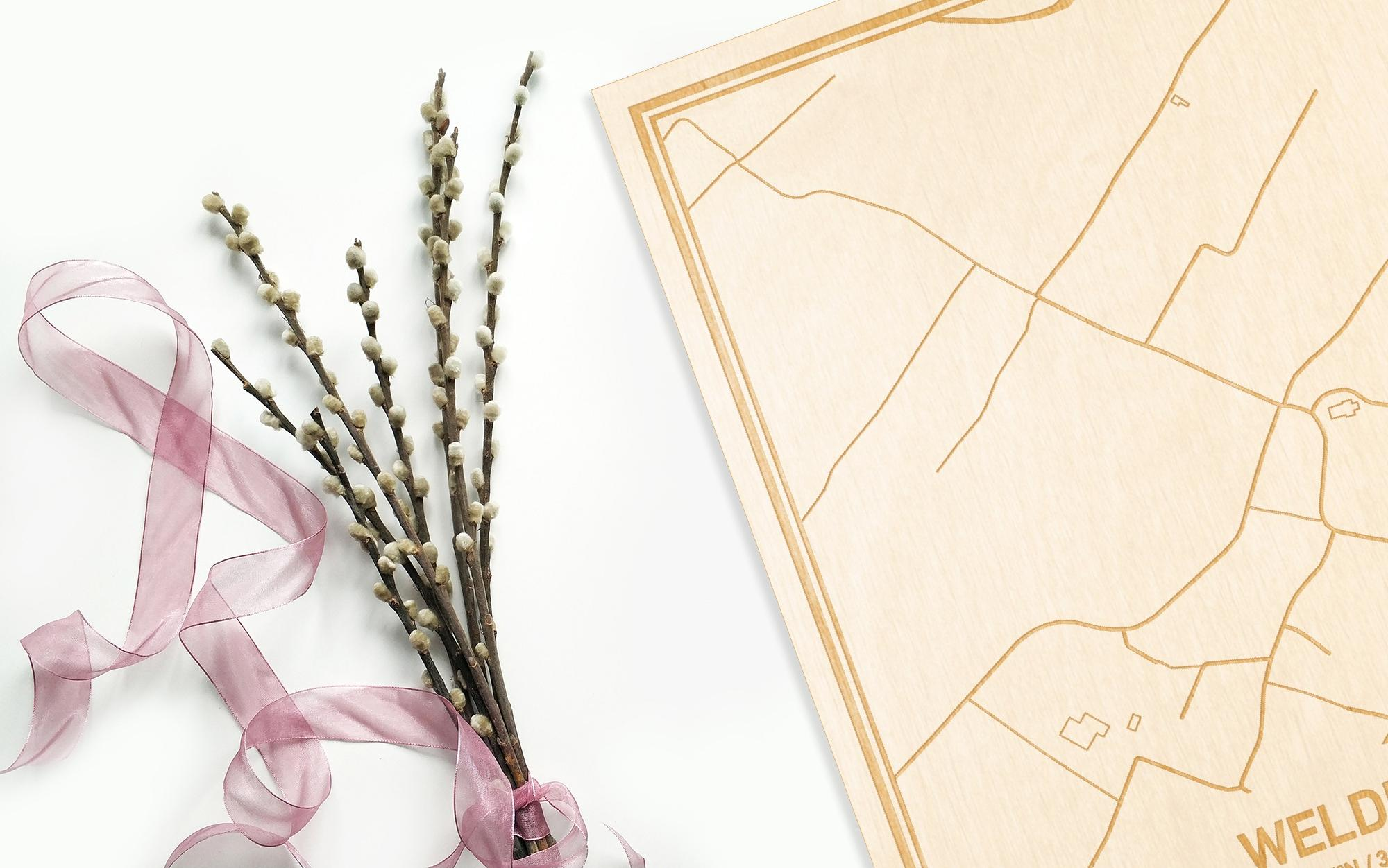 Hier ligt de houten plattegrond Welden naast een bloemetje als gepersonaliseerd cadeau voor haar.
