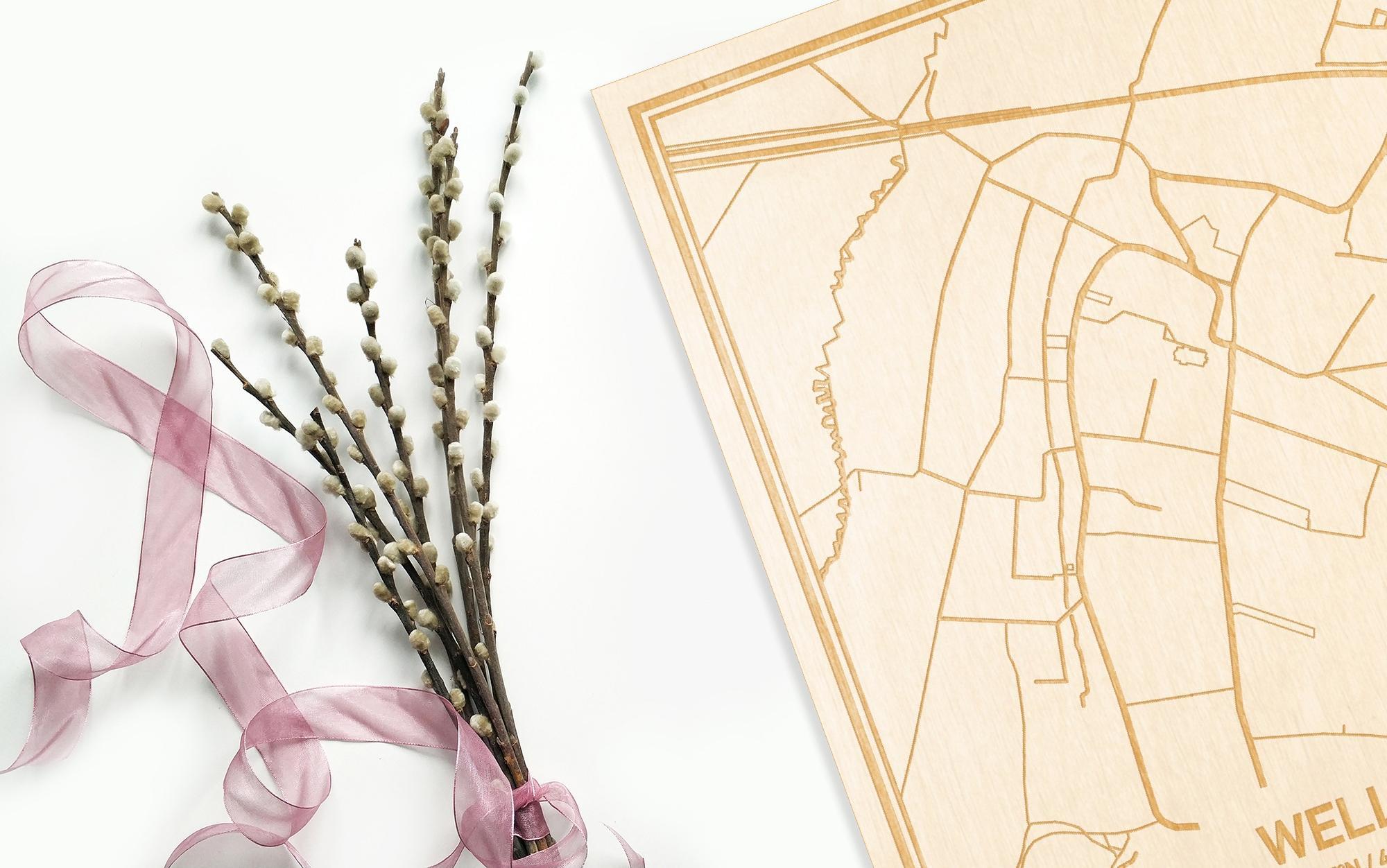 Hier ligt de houten plattegrond Welle naast een bloemetje als gepersonaliseerd cadeau voor haar.