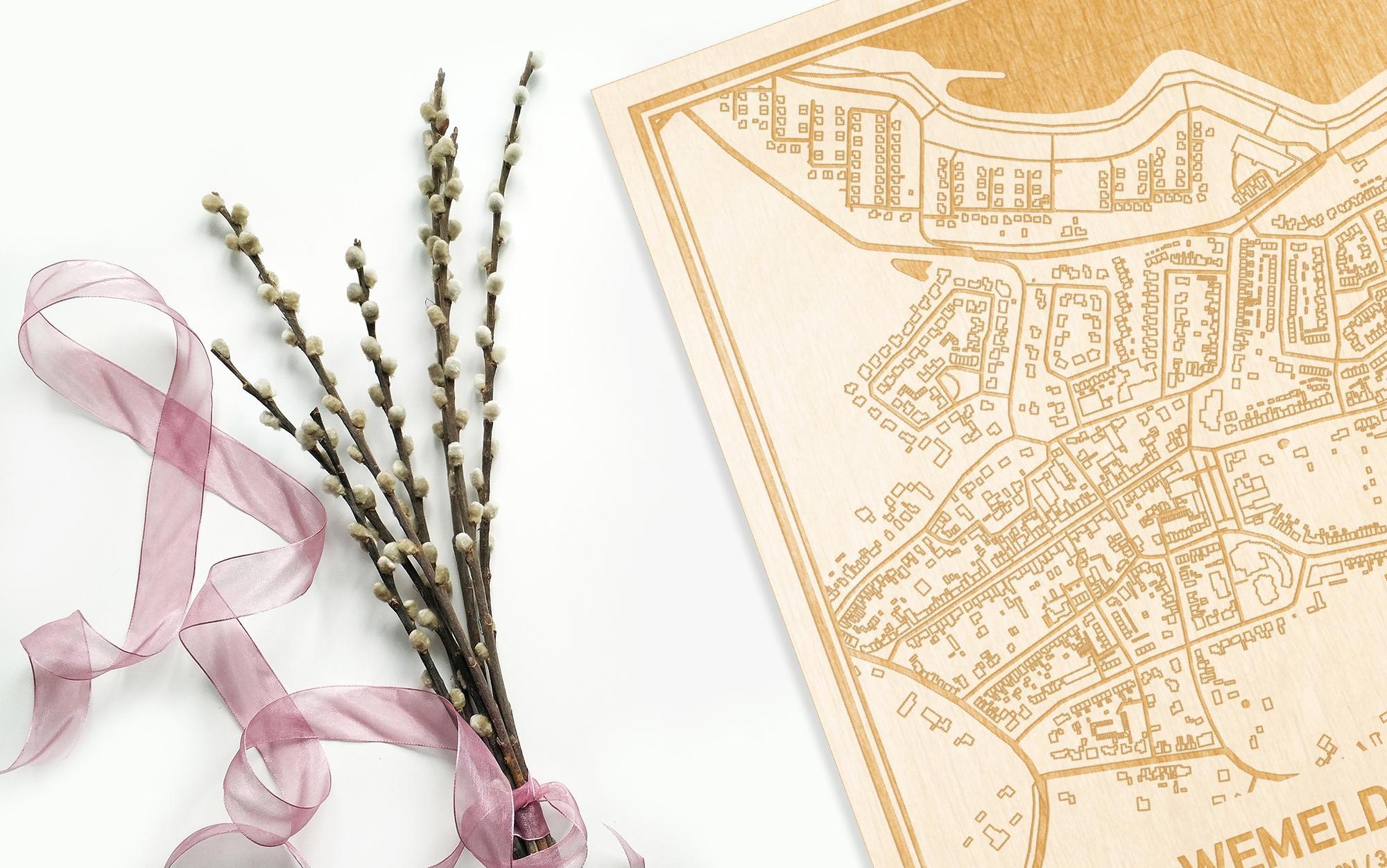 Hier ligt de houten plattegrond Wemeldinge naast een bloemetje als gepersonaliseerd cadeau voor haar.