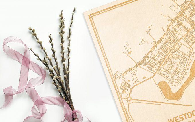 Hier ligt de houten plattegrond Westdorpe naast een bloemetje als gepersonaliseerd cadeau voor haar.