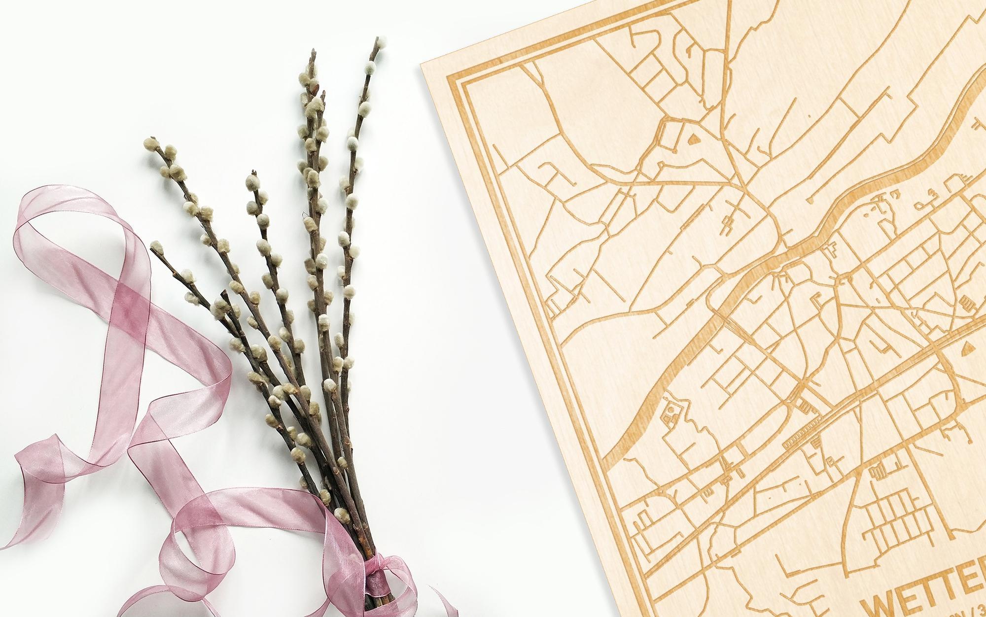 Hier ligt de houten plattegrond Wetteren naast een bloemetje als gepersonaliseerd cadeau voor haar.