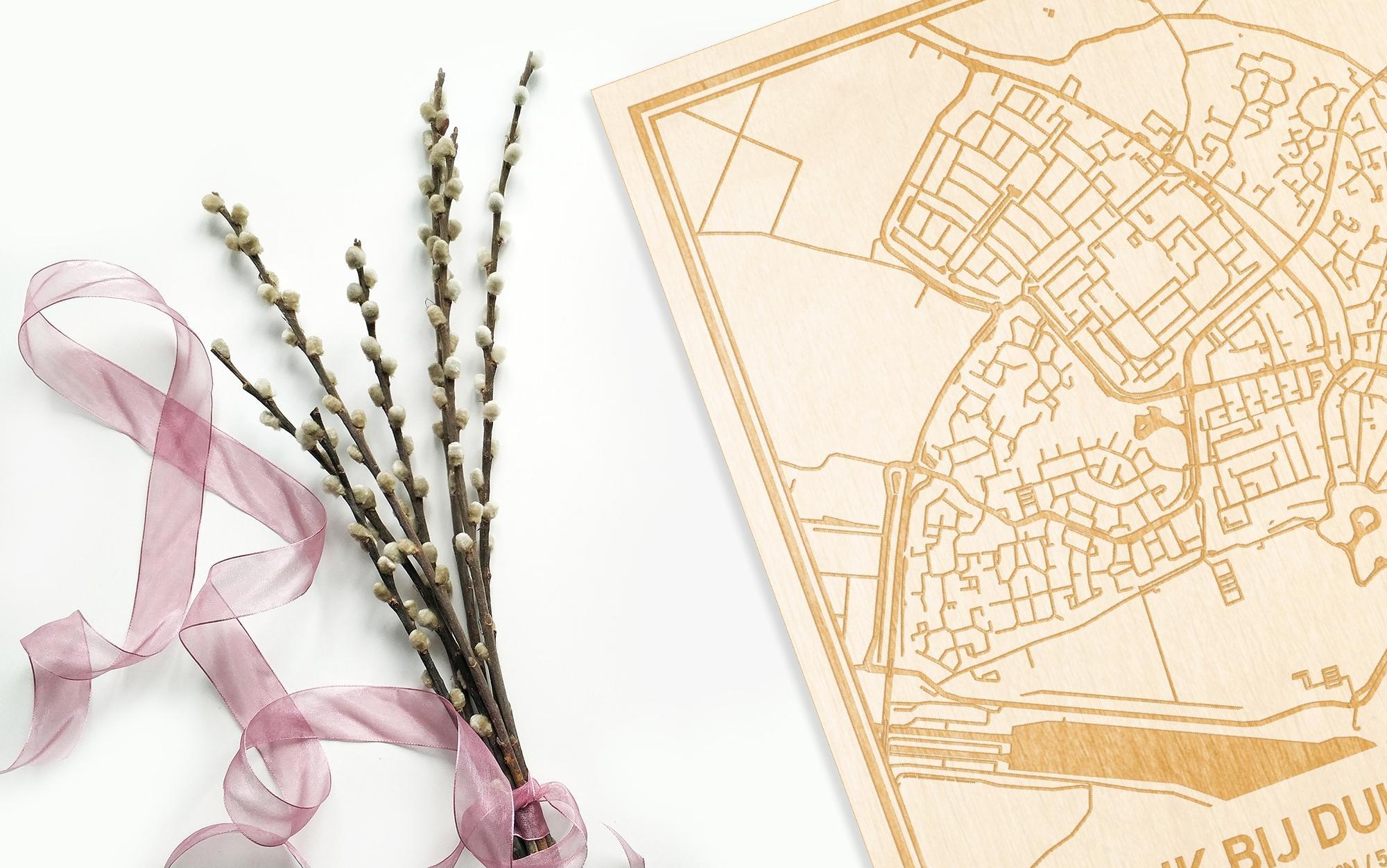 Hier ligt de houten plattegrond Wijk bij Duurstede naast een bloemetje als gepersonaliseerd cadeau voor haar.