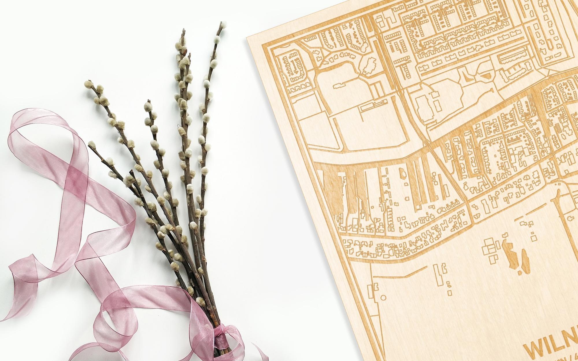 Hier ligt de houten plattegrond Wilnis naast een bloemetje als gepersonaliseerd cadeau voor haar.