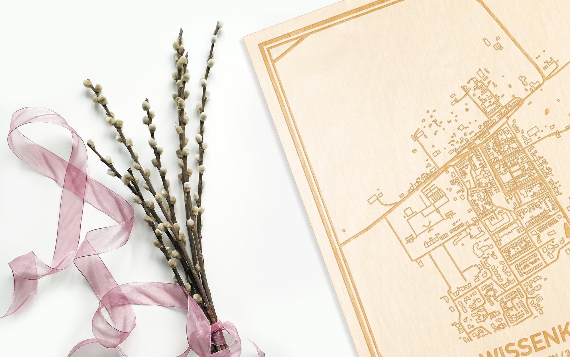Hier ligt de houten plattegrond Wissenkerke naast een bloemetje als gepersonaliseerd cadeau voor haar.