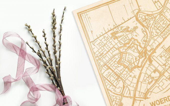 Hier ligt de houten plattegrond Woerden naast een bloemetje als gepersonaliseerd cadeau voor haar.
