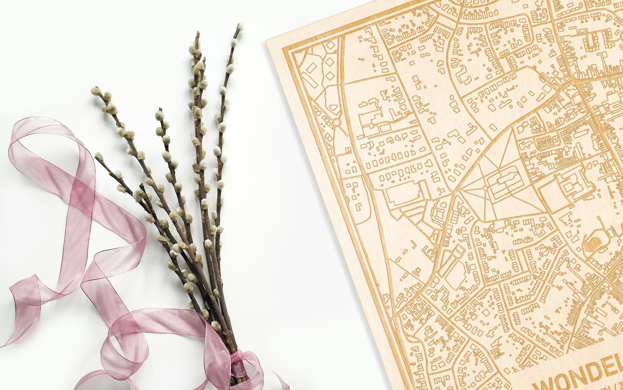 Hier ligt de houten plattegrond Wondelgem naast een bloemetje als gepersonaliseerd cadeau voor haar.