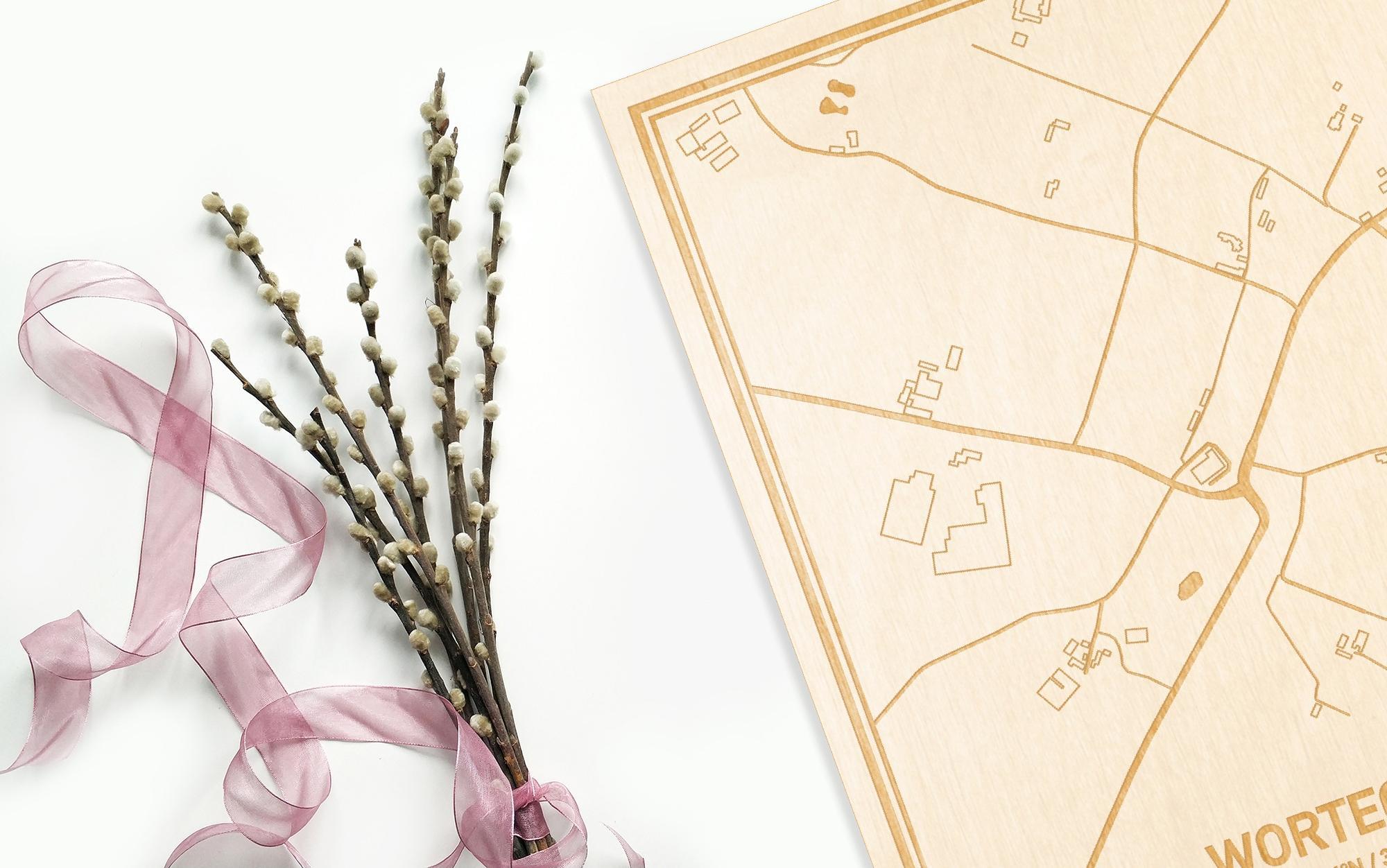 Hier ligt de houten plattegrond Wortegem naast een bloemetje als gepersonaliseerd cadeau voor haar.