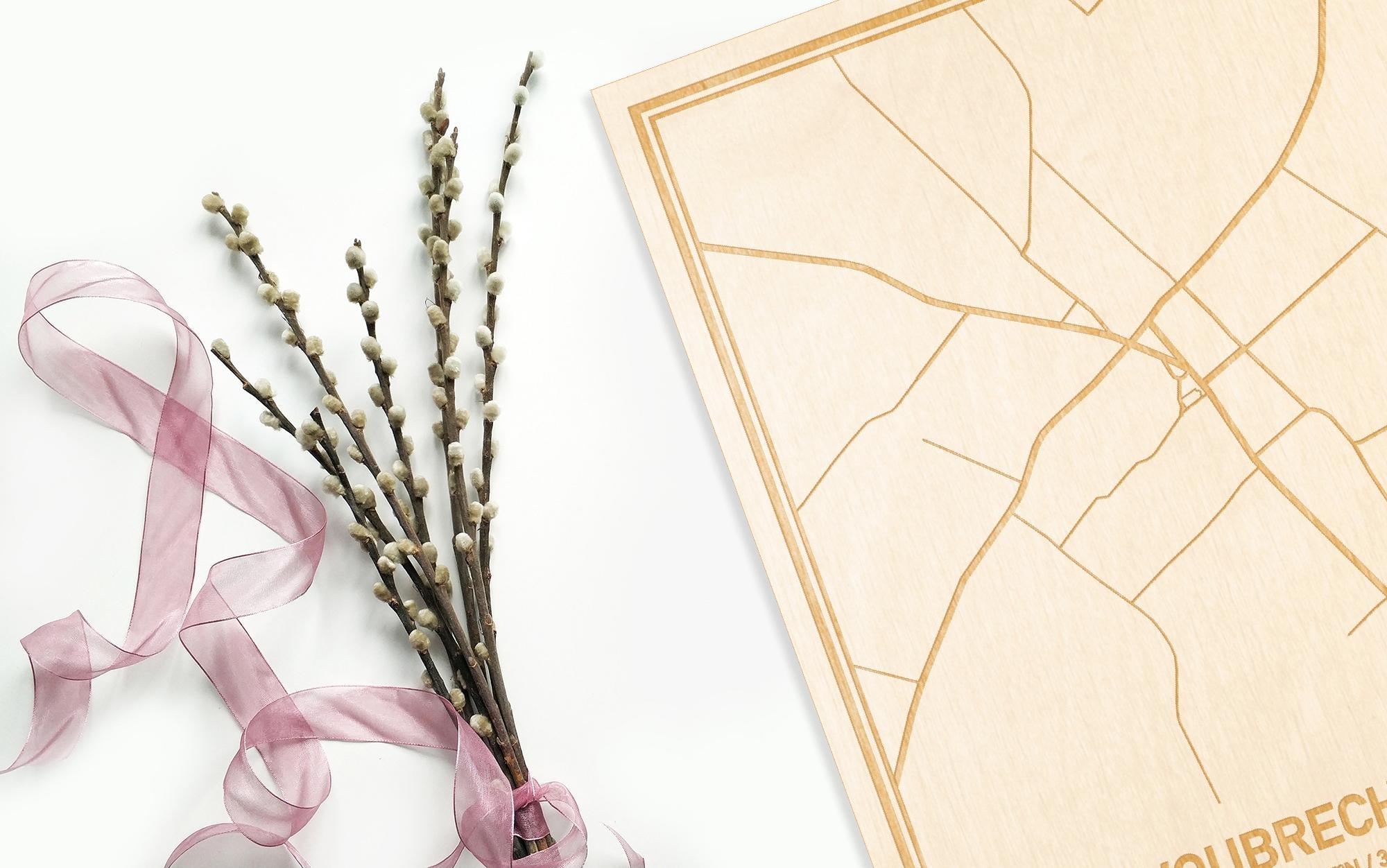 Hier ligt de houten plattegrond Woubrechtegem naast een bloemetje als gepersonaliseerd cadeau voor haar.