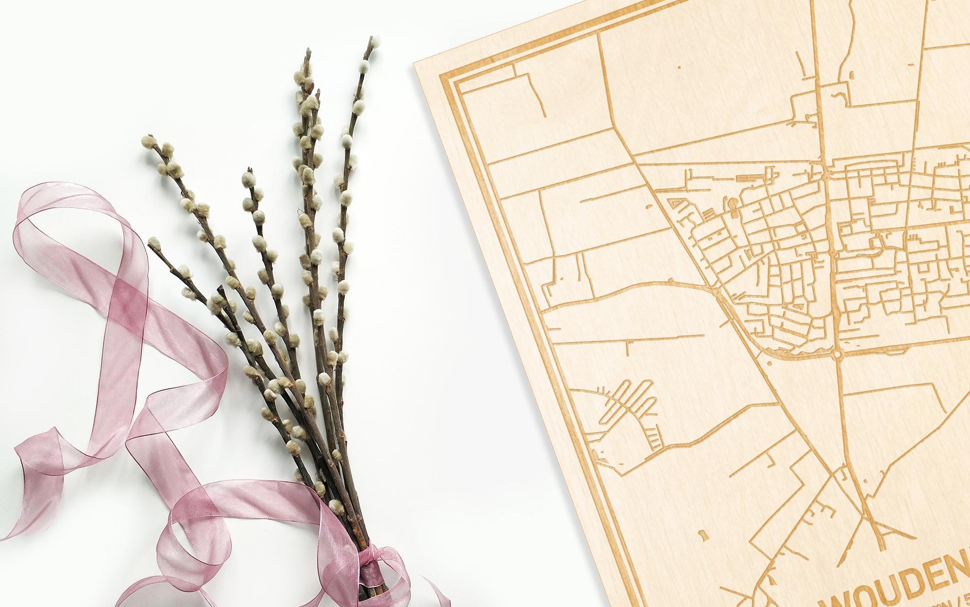 Hier ligt de houten plattegrond Woudenberg naast een bloemetje als gepersonaliseerd cadeau voor haar.