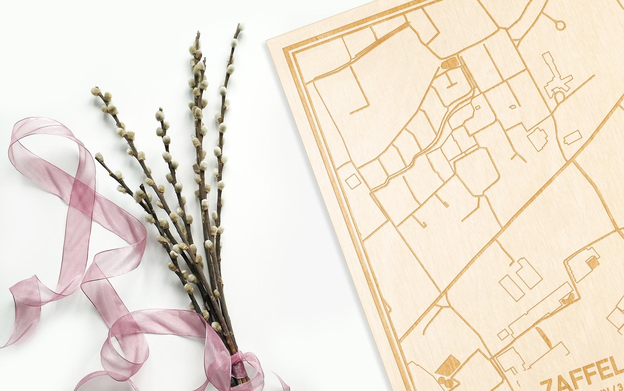 Hier ligt de houten plattegrond Zaffelare naast een bloemetje als gepersonaliseerd cadeau voor haar.