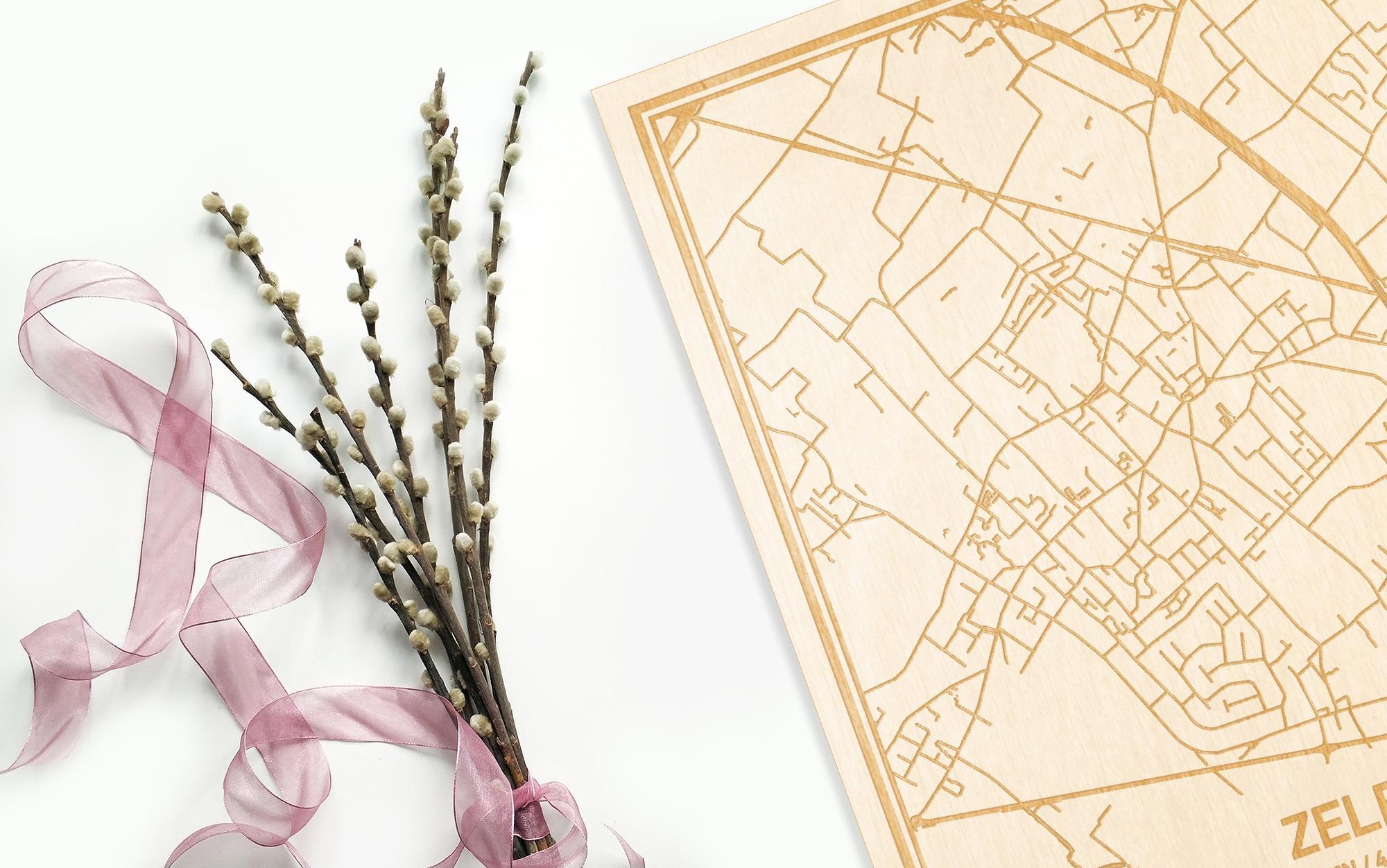 Hier ligt de houten plattegrond Zele naast een bloemetje als gepersonaliseerd cadeau voor haar.
