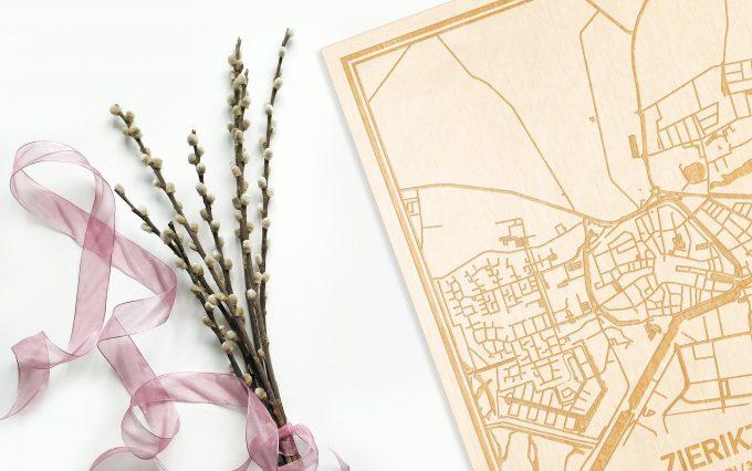 Hier ligt de houten plattegrond Zierikzee naast een bloemetje als gepersonaliseerd cadeau voor haar.