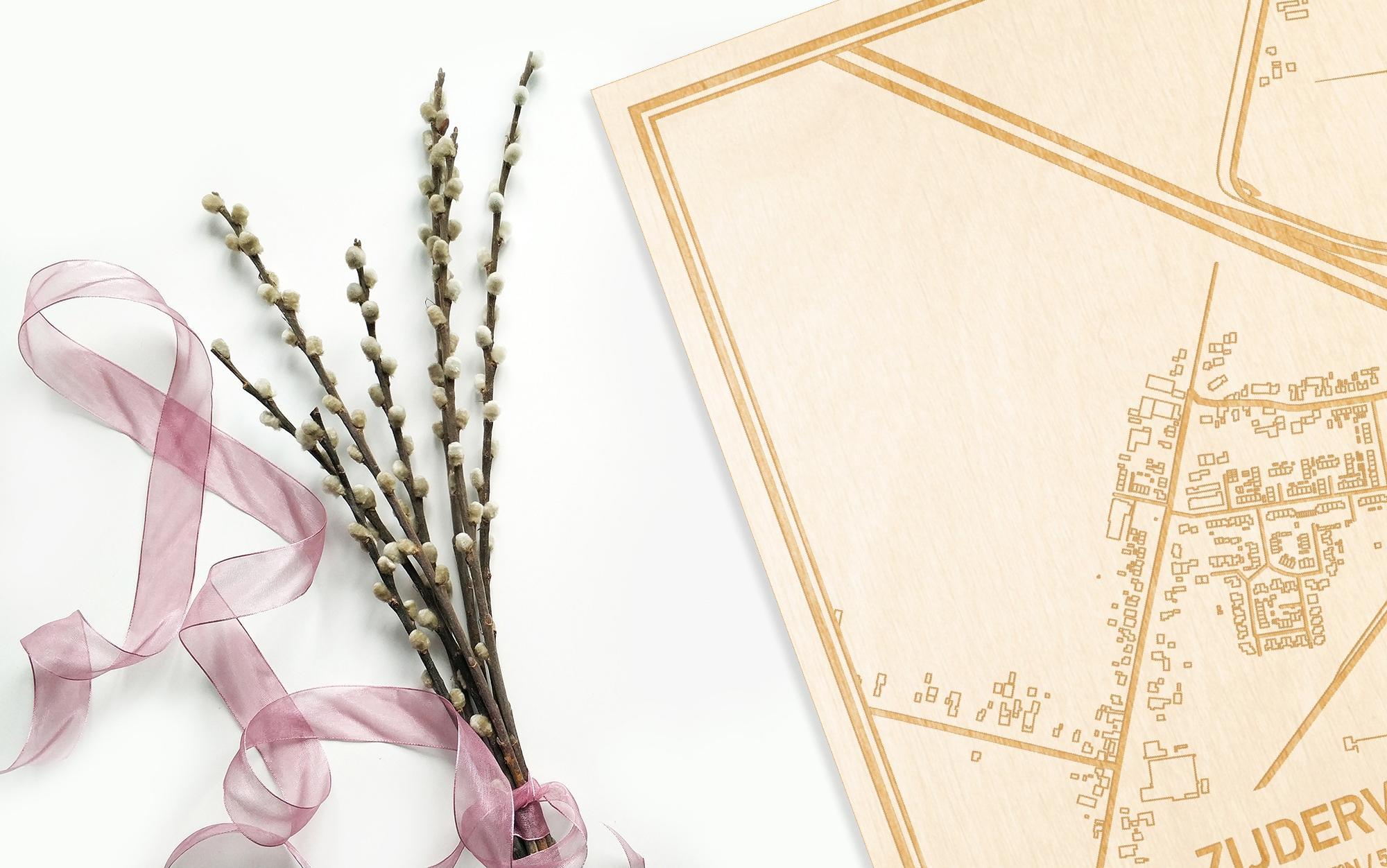Hier ligt de houten plattegrond Zijderveld naast een bloemetje als gepersonaliseerd cadeau voor haar.