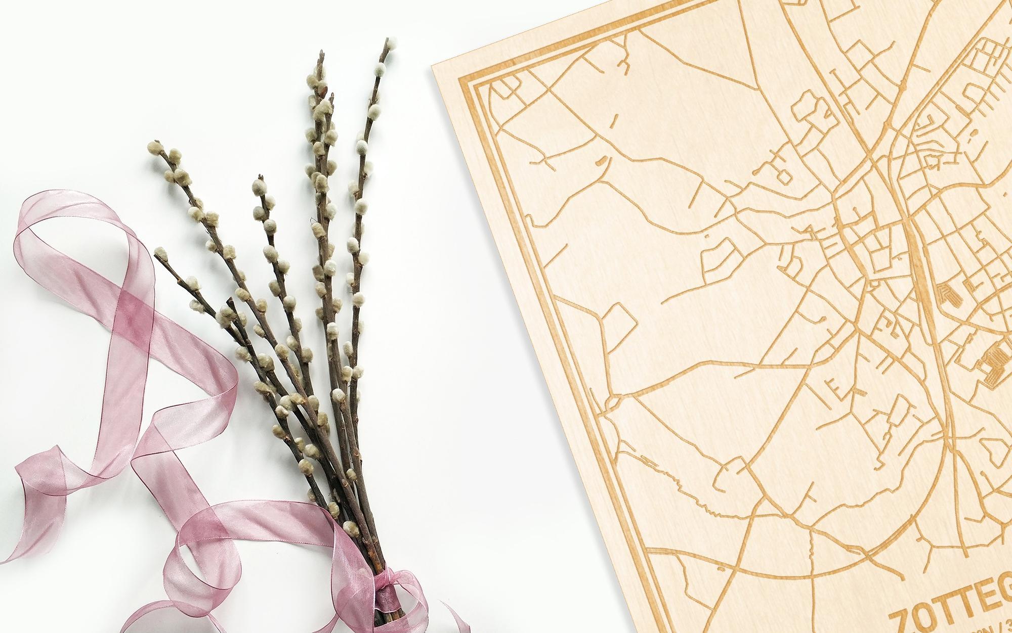 Hier ligt de houten plattegrond Zottegem naast een bloemetje als gepersonaliseerd cadeau voor haar.