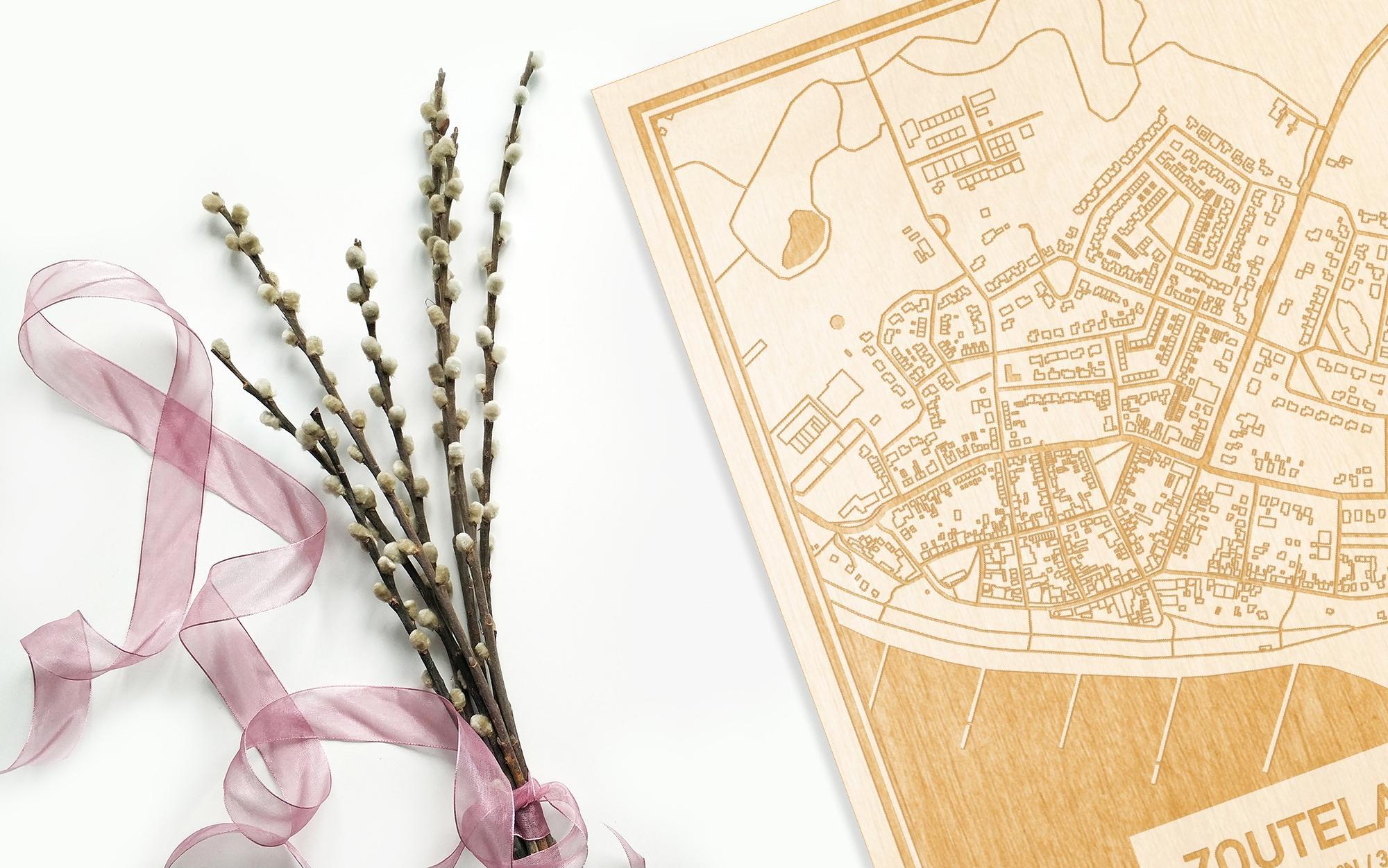 Hier ligt de houten plattegrond Zoutelande naast een bloemetje als gepersonaliseerd cadeau voor haar.