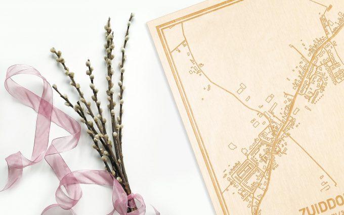 Hier ligt de houten plattegrond Zuiddorpe naast een bloemetje als gepersonaliseerd cadeau voor haar.