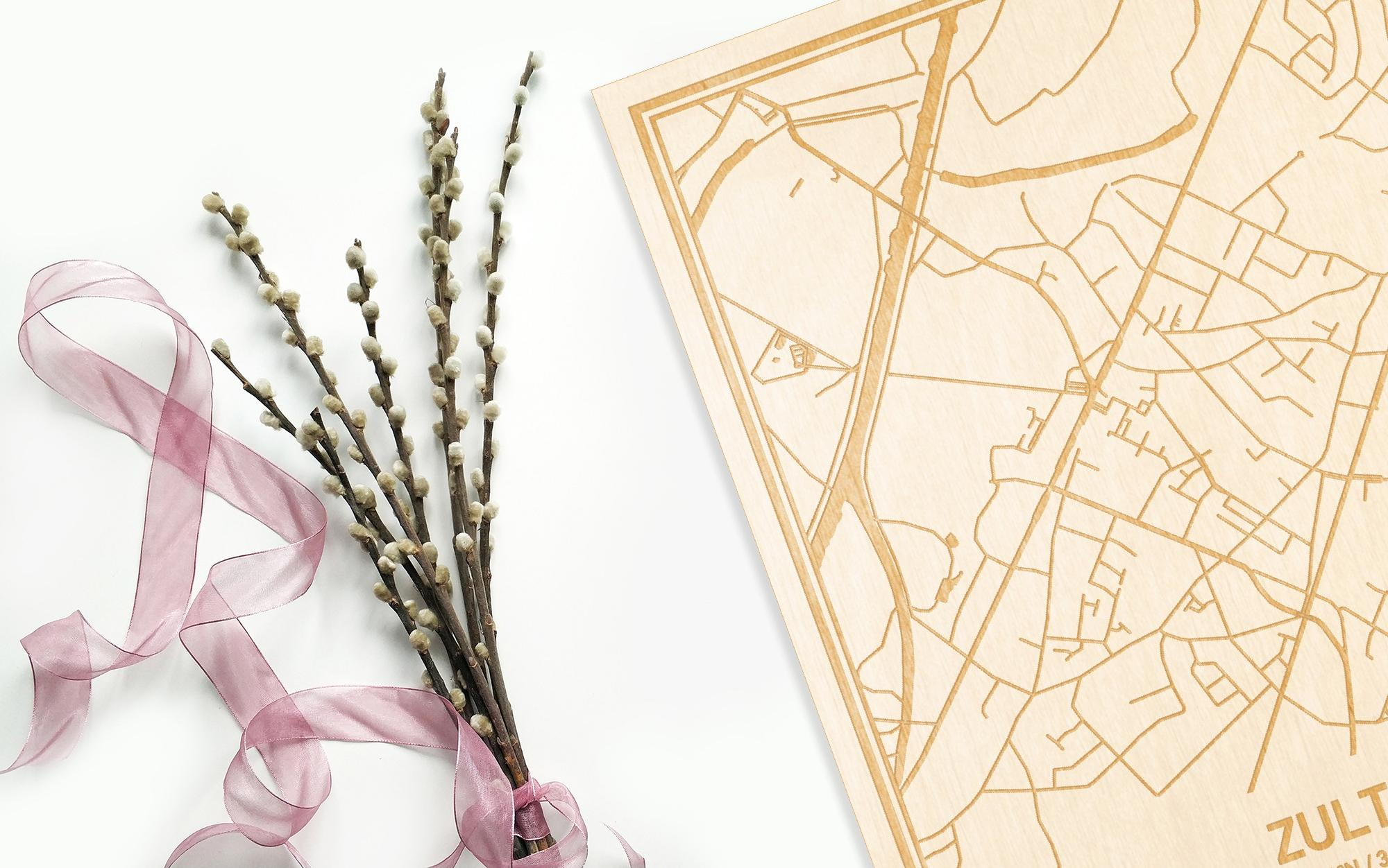 Hier ligt de houten plattegrond Zulte naast een bloemetje als gepersonaliseerd cadeau voor haar.