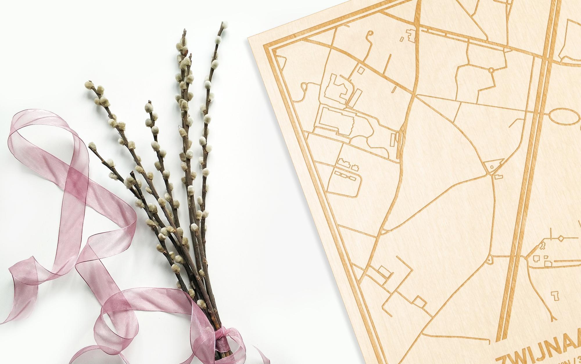 Hier ligt de houten plattegrond Zwijnaarde naast een bloemetje als gepersonaliseerd cadeau voor haar.