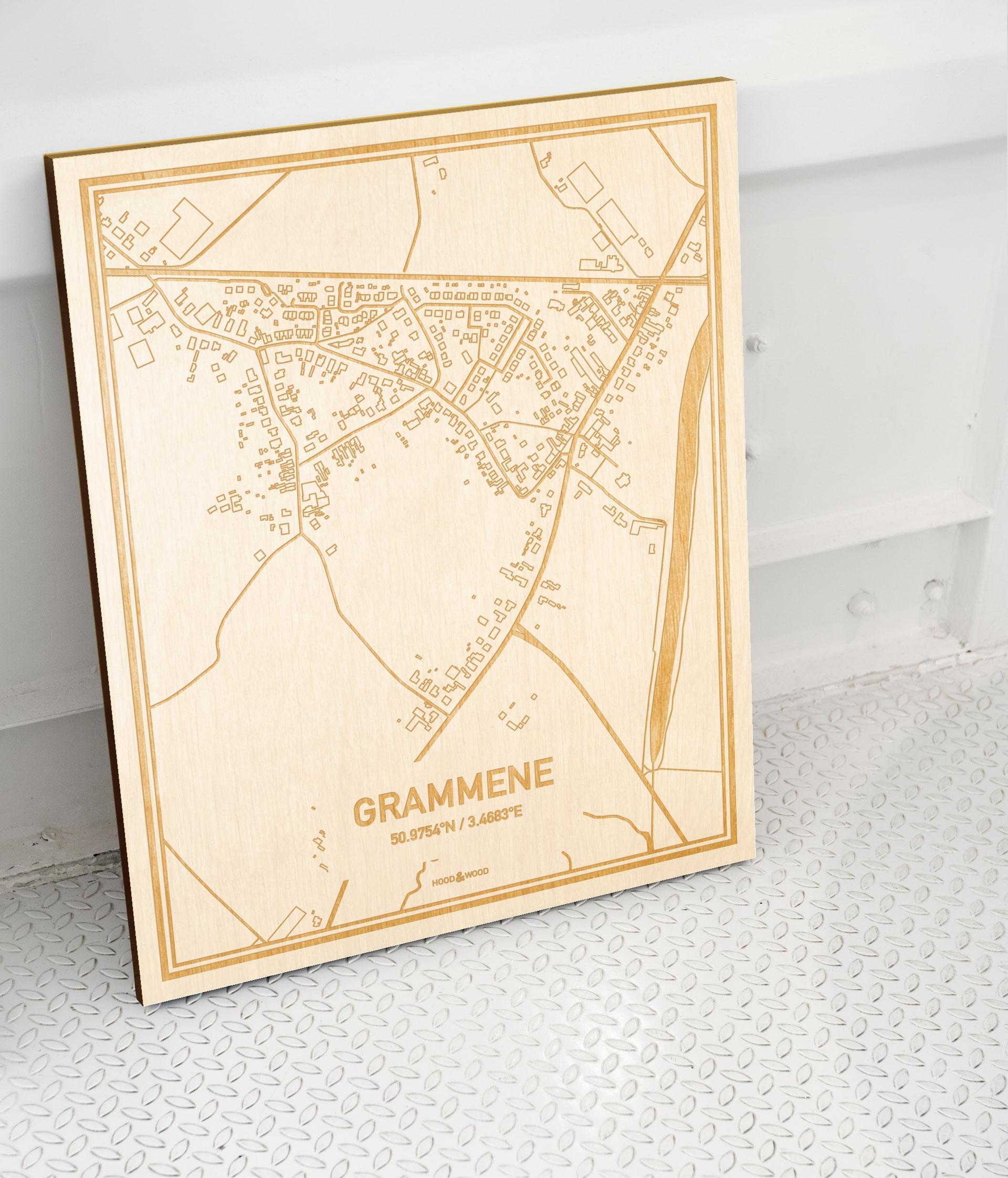 Plattegrond Grammene als prachtige houten wanddecoratie. Het warme hout contrasteert mooi met de witte muur.