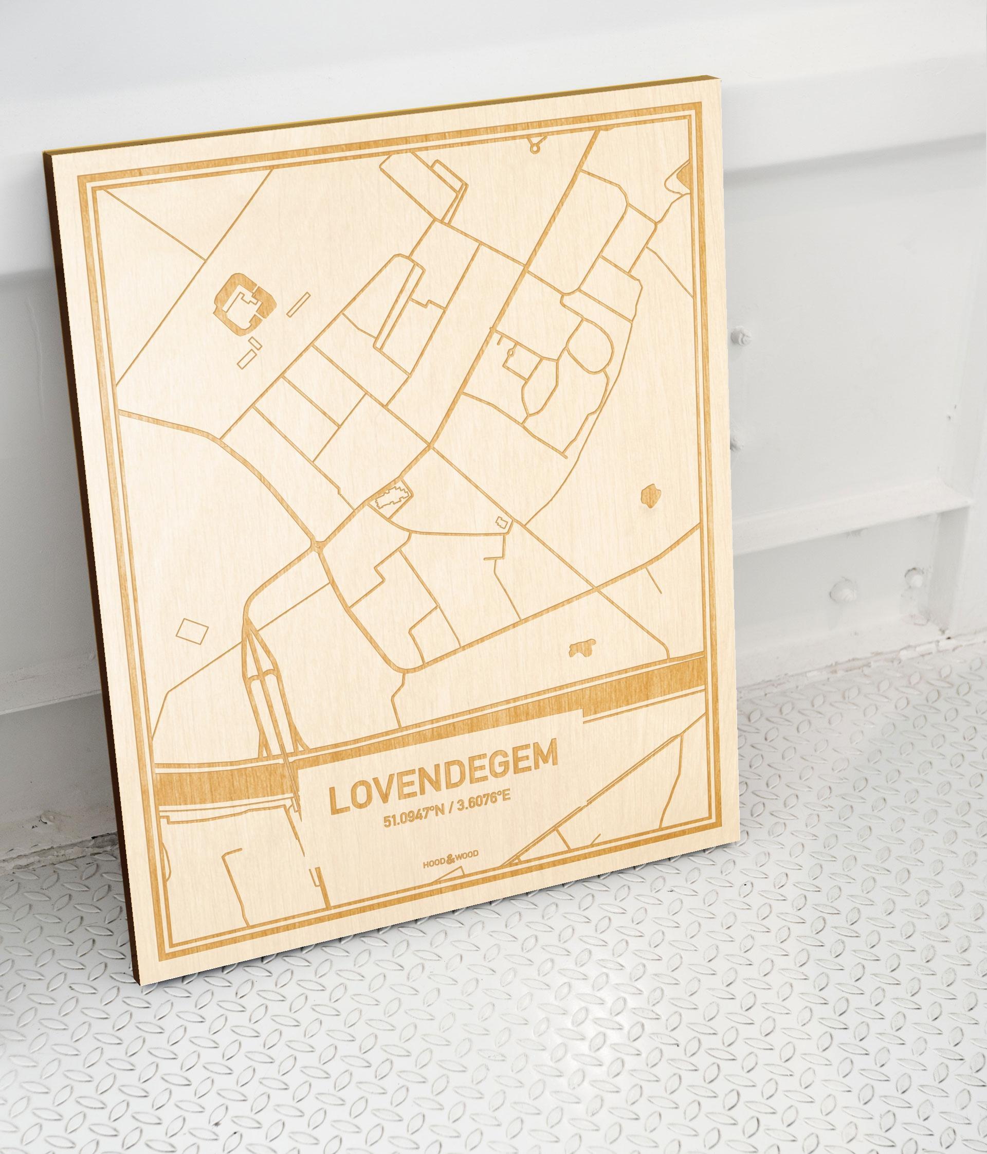Plattegrond Lovendegem als prachtige houten wanddecoratie. Het warme hout contrasteert mooi met de witte muur.