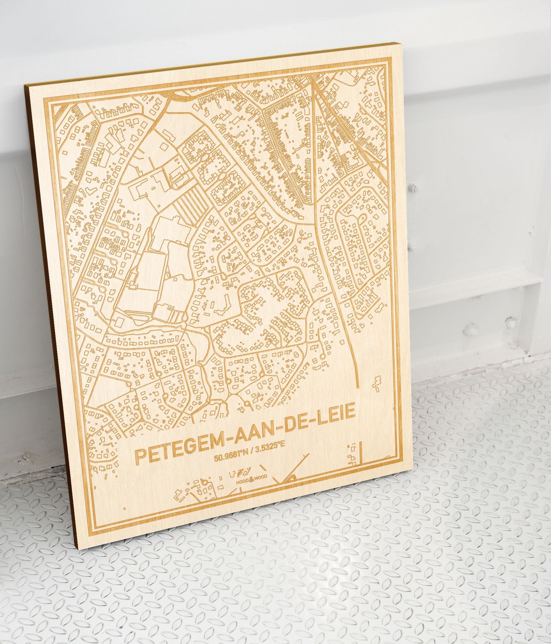 Plattegrond Petegem-Aan-De-Leie als prachtige houten wanddecoratie. Het warme hout contrasteert mooi met de witte muur.