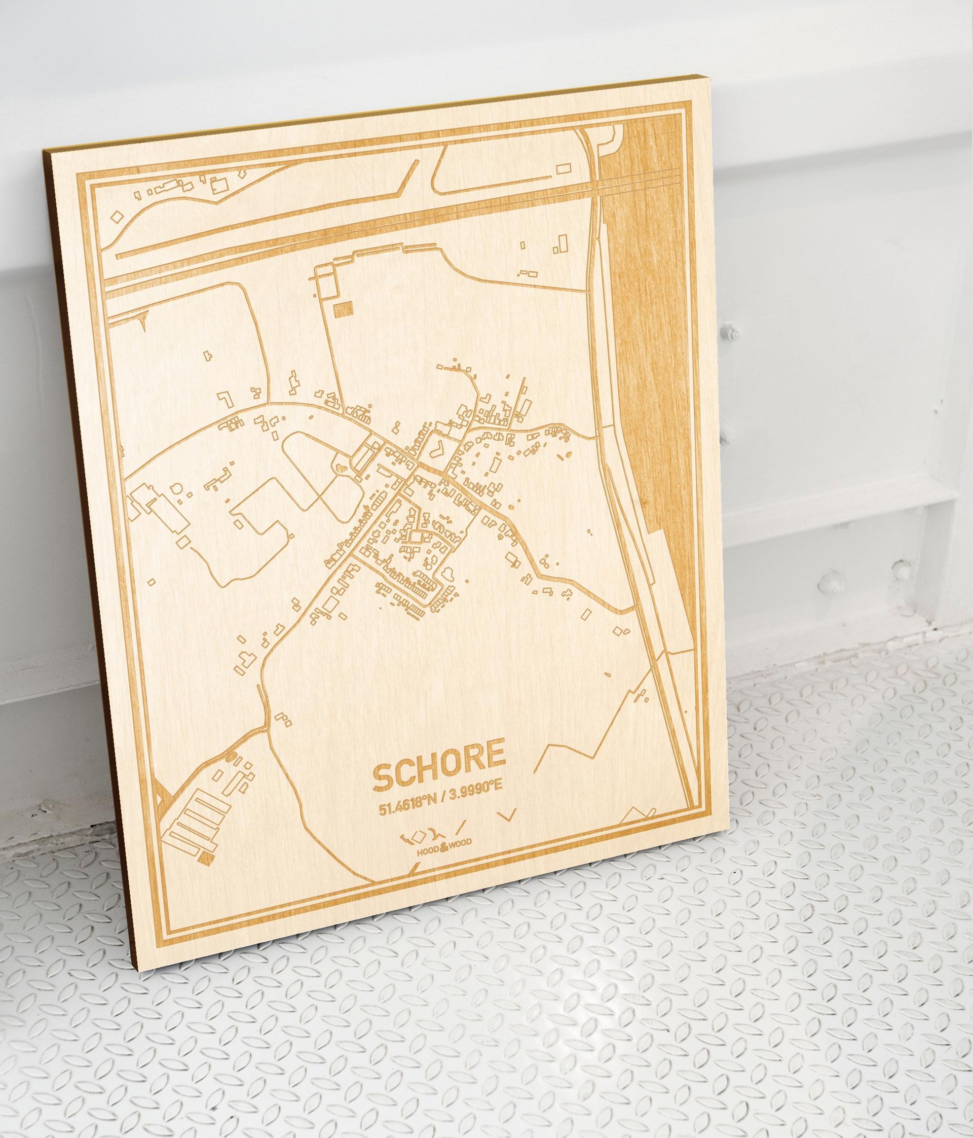 Plattegrond Schore als prachtige houten wanddecoratie. Het warme hout contrasteert mooi met de witte muur.