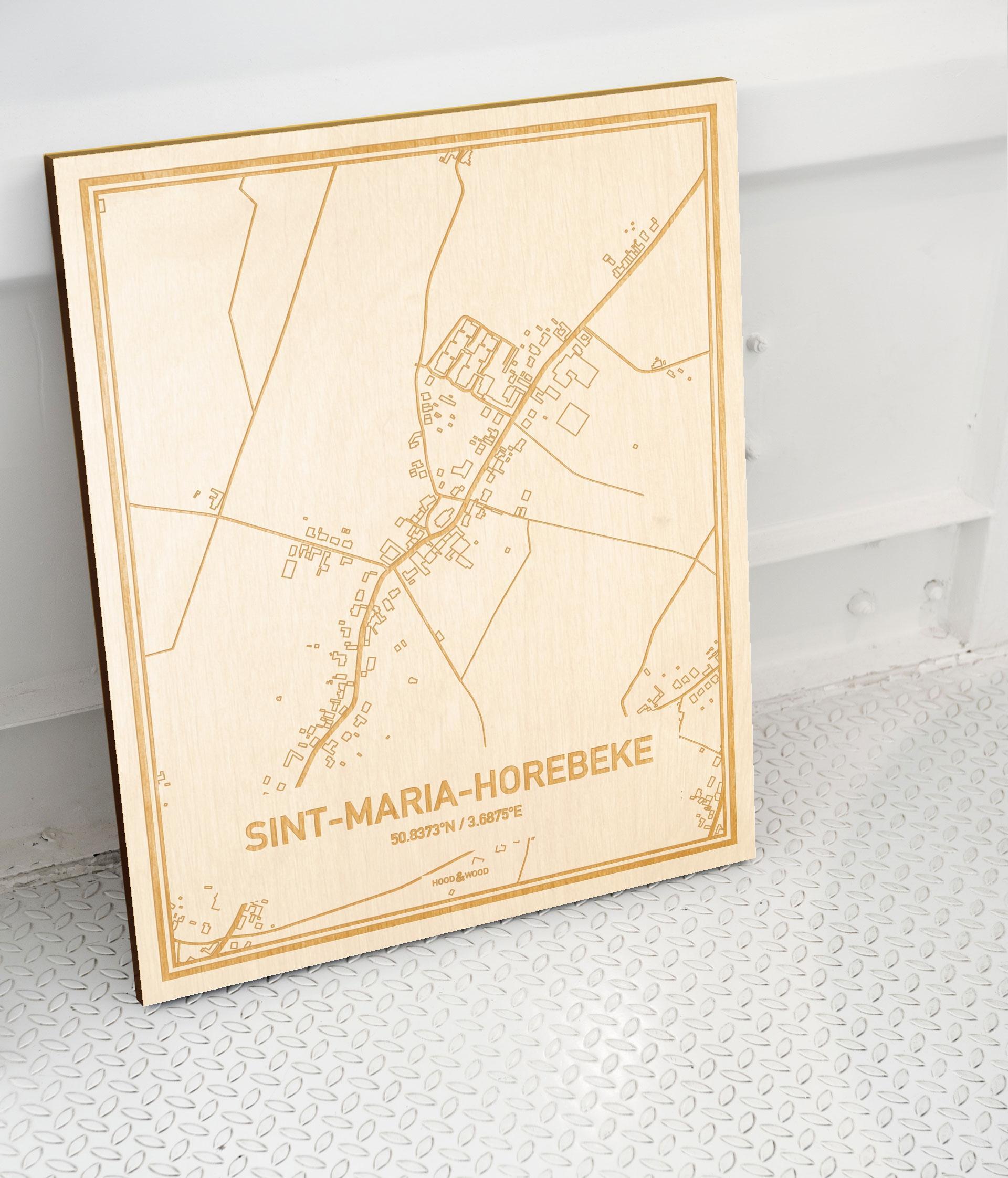Plattegrond Sint-Maria-Horebeke als prachtige houten wanddecoratie. Het warme hout contrasteert mooi met de witte muur.