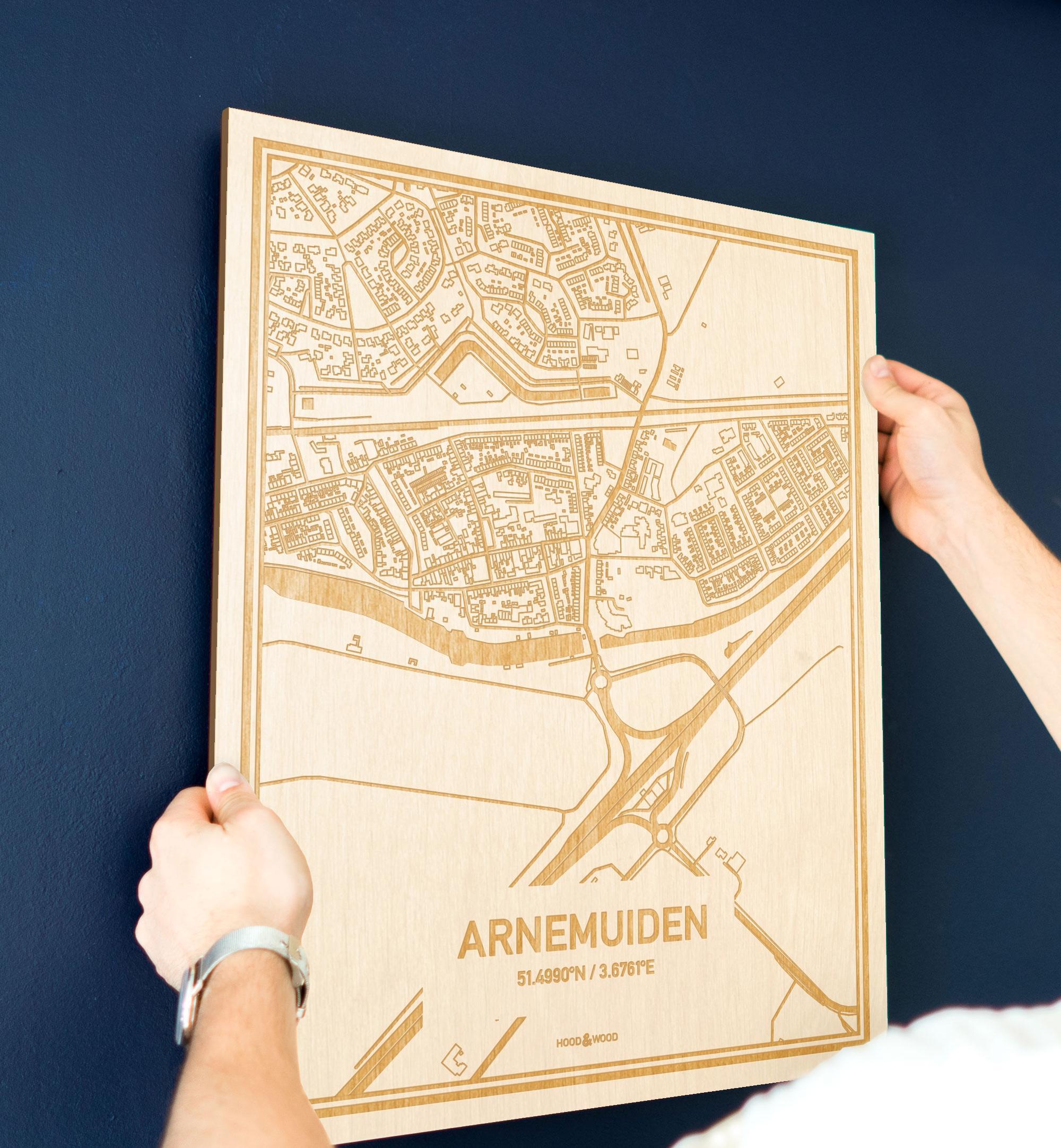 Een man hangt de houten plattegrond Arnemuiden aan zijn blauwe muur ter decoratie. Je ziet alleen zijn handen de kaart van deze prachtige in Zeeland vasthouden.
