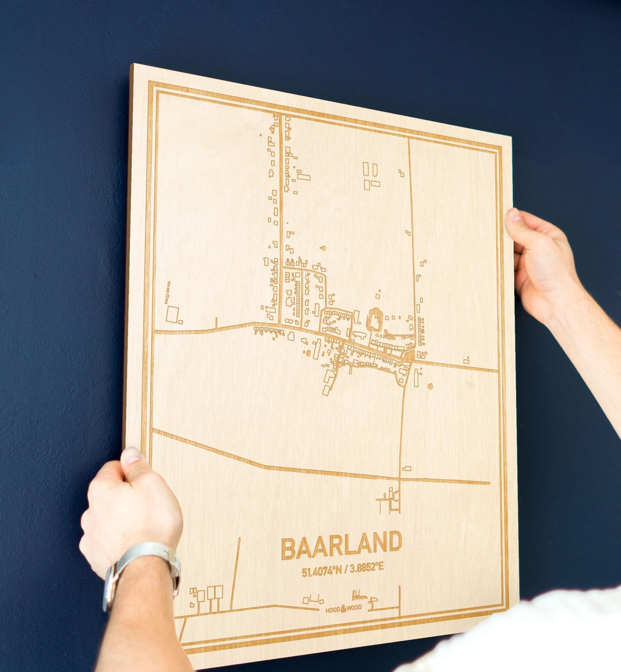 Een man hangt de houten plattegrond Baarland aan zijn blauwe muur ter decoratie. Je ziet alleen zijn handen de kaart van deze unieke in Zeeland vasthouden.