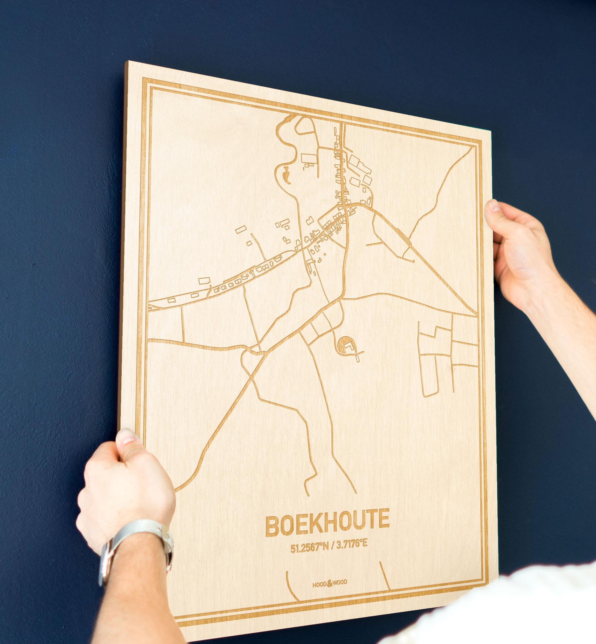 Een man hangt de houten plattegrond Boekhoute aan zijn blauwe muur ter decoratie. Je ziet alleen zijn handen de kaart van deze unieke in Oost-Vlaanderen  vasthouden.