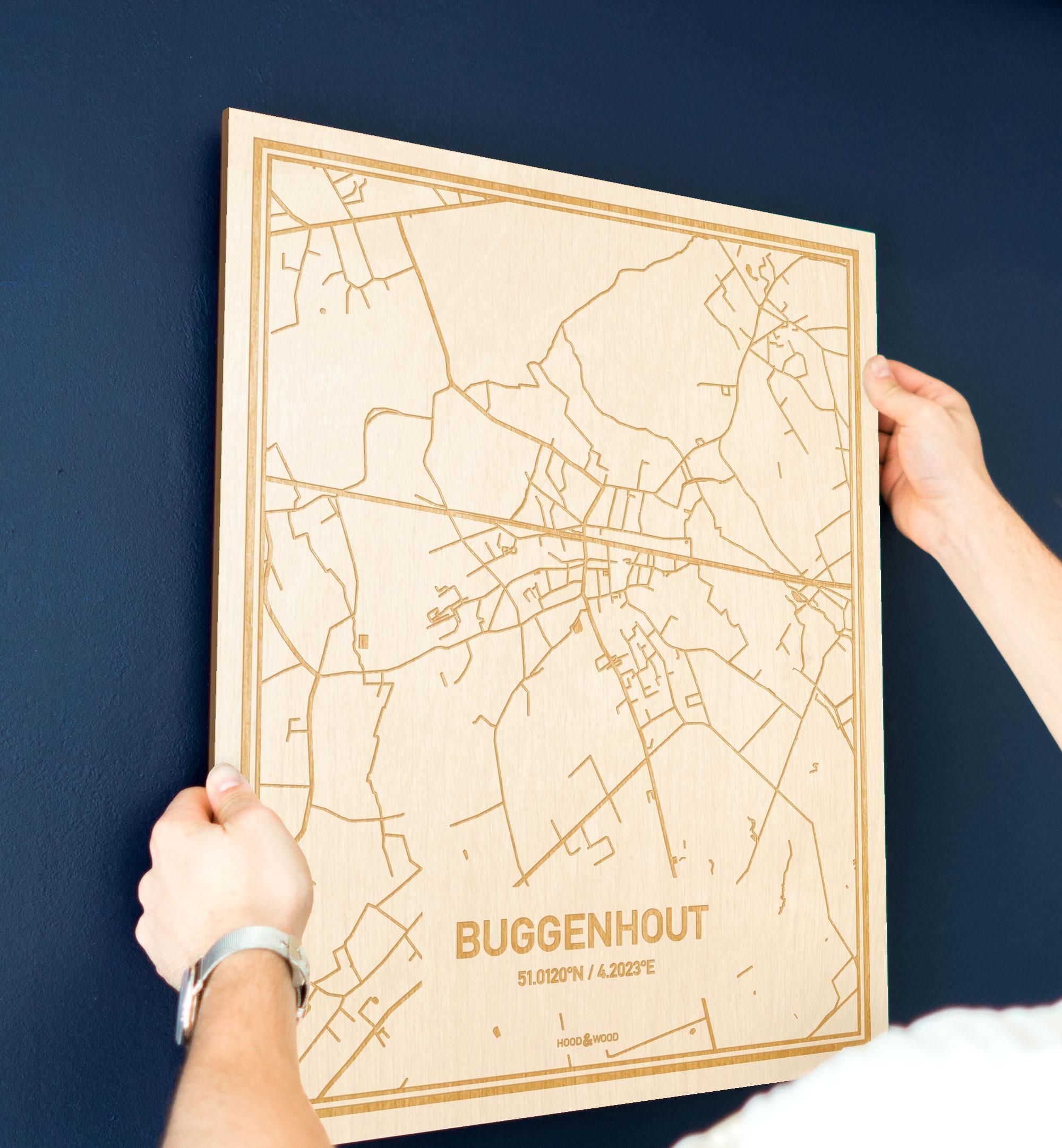 Een man hangt de houten plattegrond Buggenhout aan zijn blauwe muur ter decoratie. Je ziet alleen zijn handen de kaart van deze originele in Oost-Vlaanderen  vasthouden.