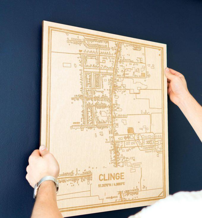 Een man hangt de houten plattegrond Clinge aan zijn blauwe muur ter decoratie. Je ziet alleen zijn handen de kaart van deze schitterende in Zeeland vasthouden.