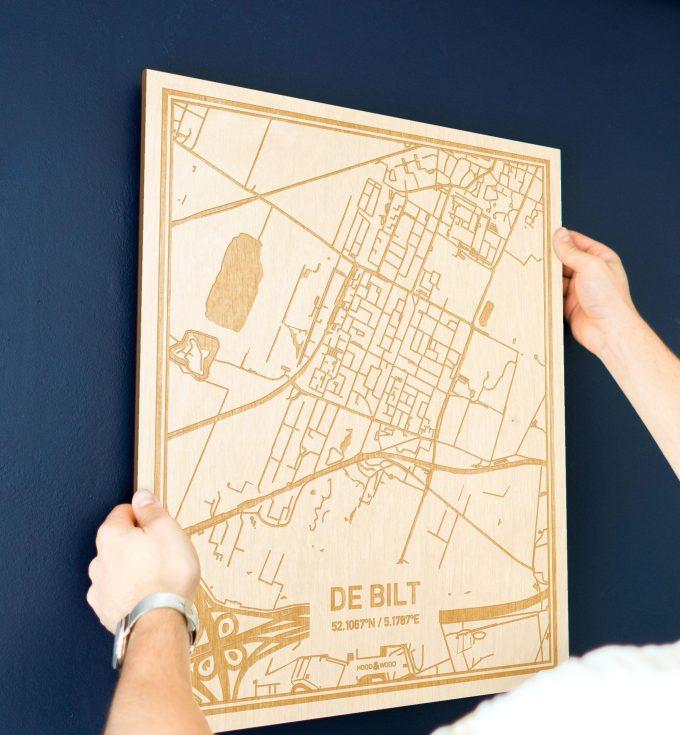 Een man hangt de houten plattegrond De Bilt aan zijn blauwe muur ter decoratie. Je ziet alleen zijn handen de kaart van deze moderne in Utrecht vasthouden.